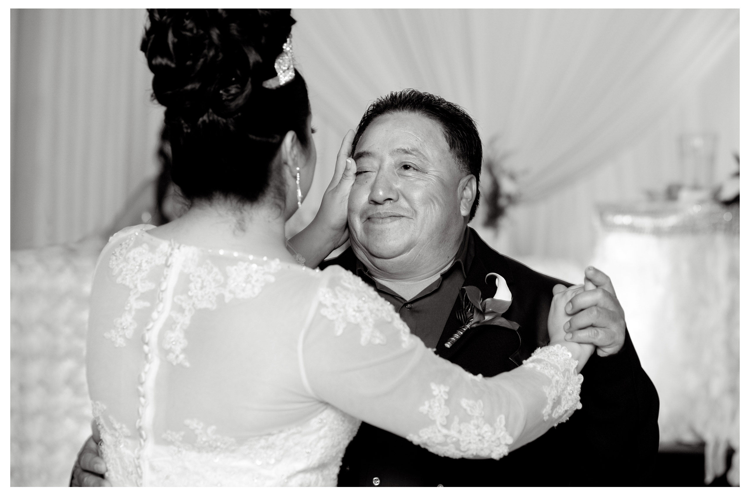 michigan wedding photographer takes photojournalists photos of a bride wiping a tear from her father's cheek during their father daughter dance in this Mexican wedding in Detroit, Michigan.