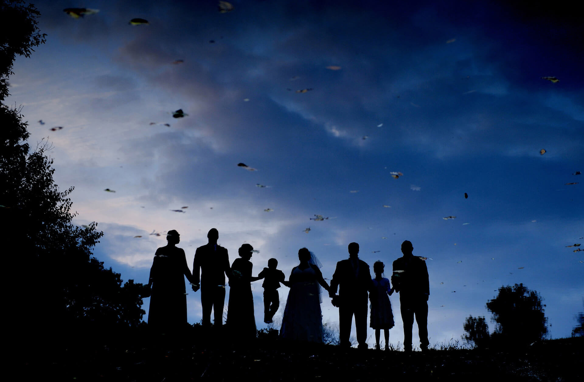 Michigan wedding photographer photographs in a unique, creative way. This is a photo of the wedding party reflected in a pond in the fall at sunset.