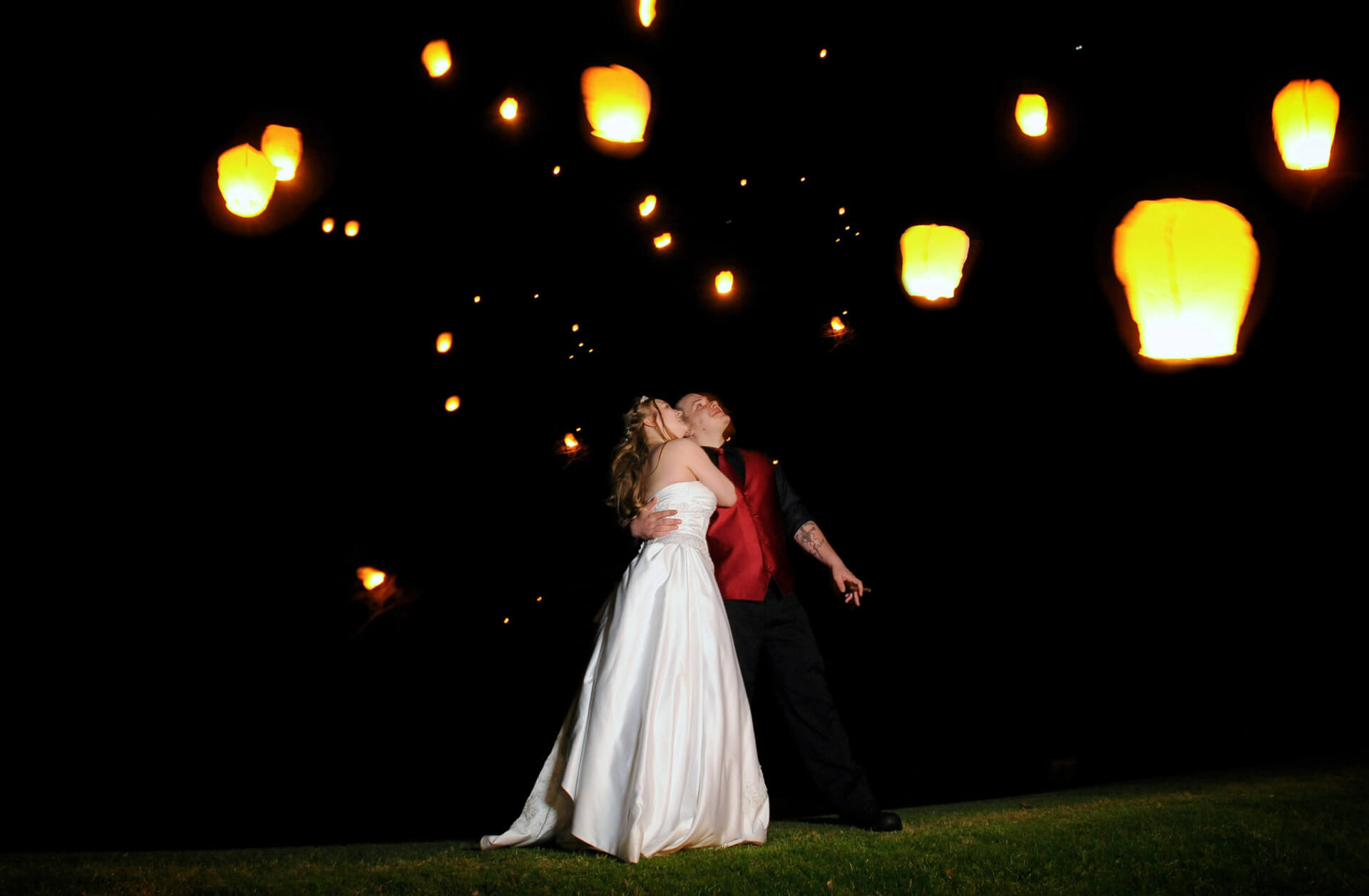 michigan wedding photographer takes unique portraits of chinese lanterns leaving after their country club wedding.