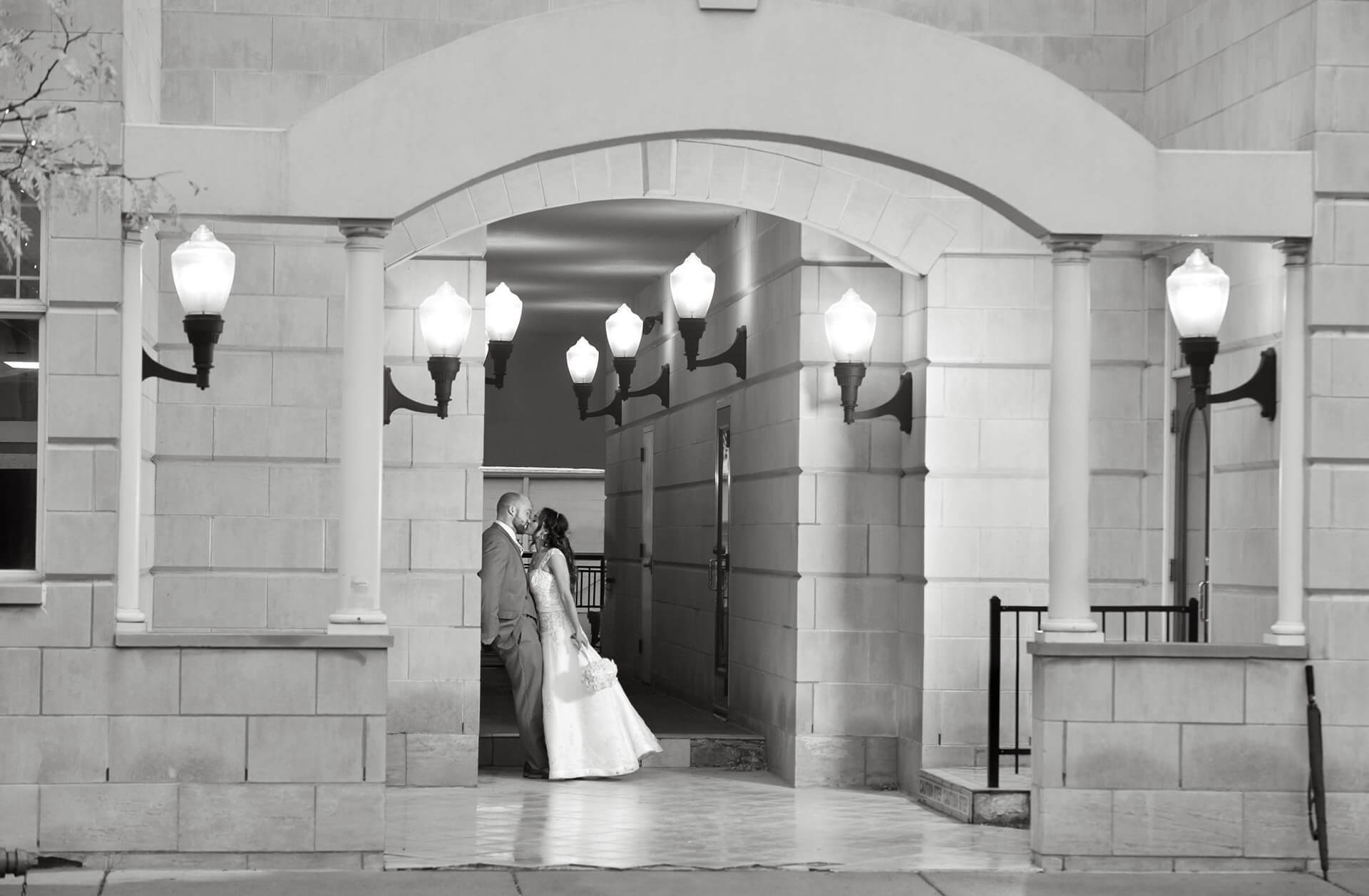 Bride and Groom snuggle and keep out of the rain in Plymouth, Michigan during their wedding.