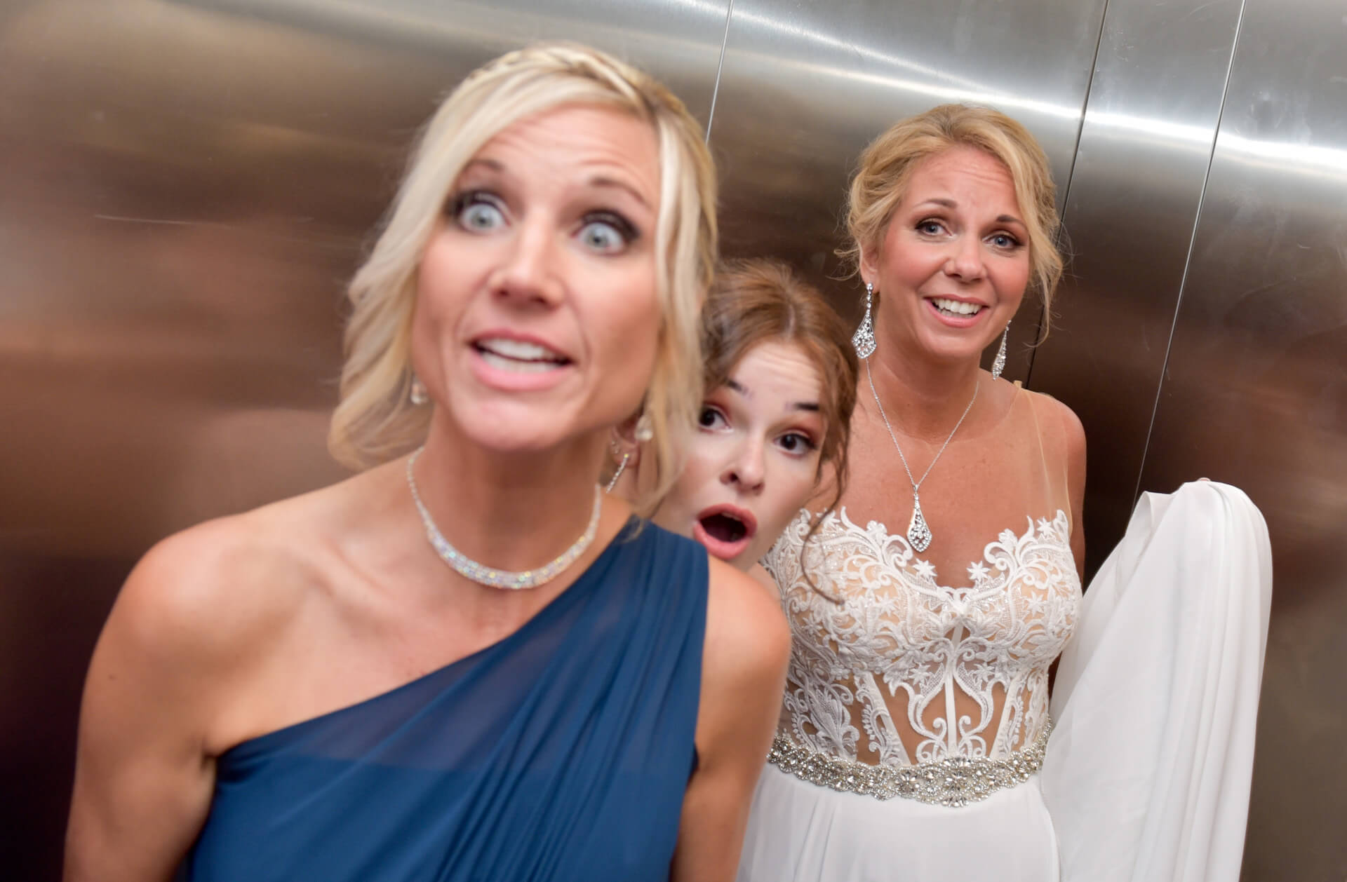 Documentary wedding photo of the wedding party reacting as the elevator doors shut on the rest of the wedding party in Detroit, Michigan.