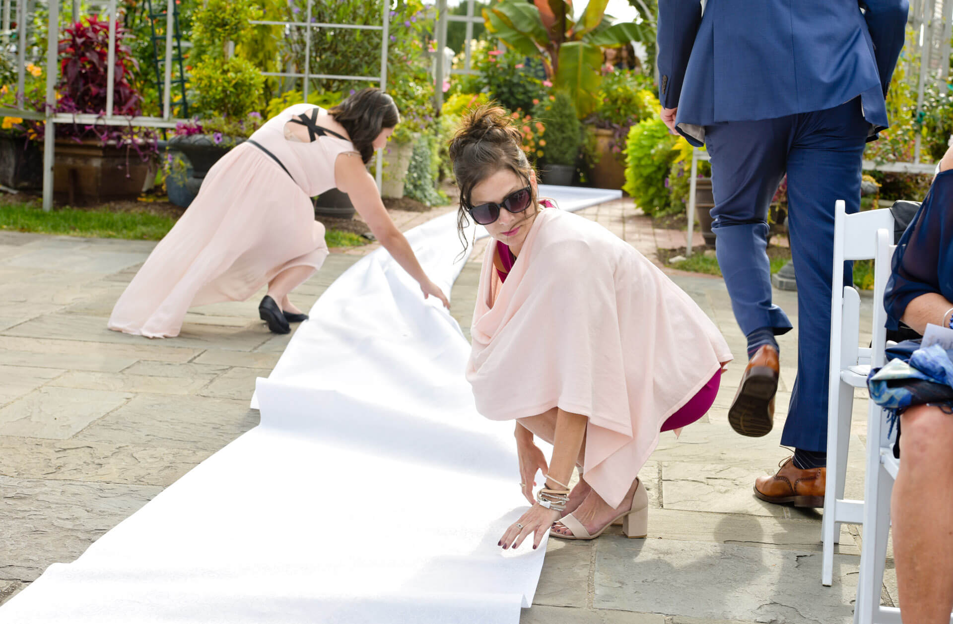 Documentary wedding photo of guests jumping in to adjust aisle runner after the wind picks up in Taylor, Michigan.