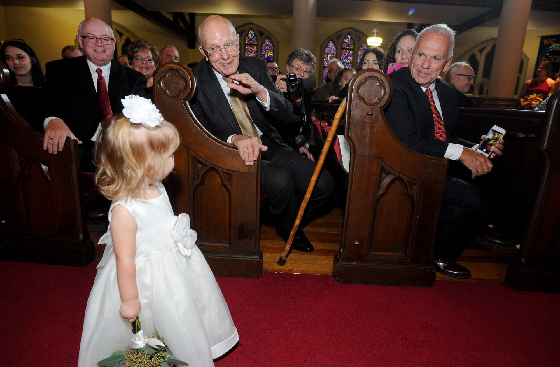 Documentary wedding photo of guests waving to the flower girl as she makes her way down the aisle in Royal Oak, Michigan.