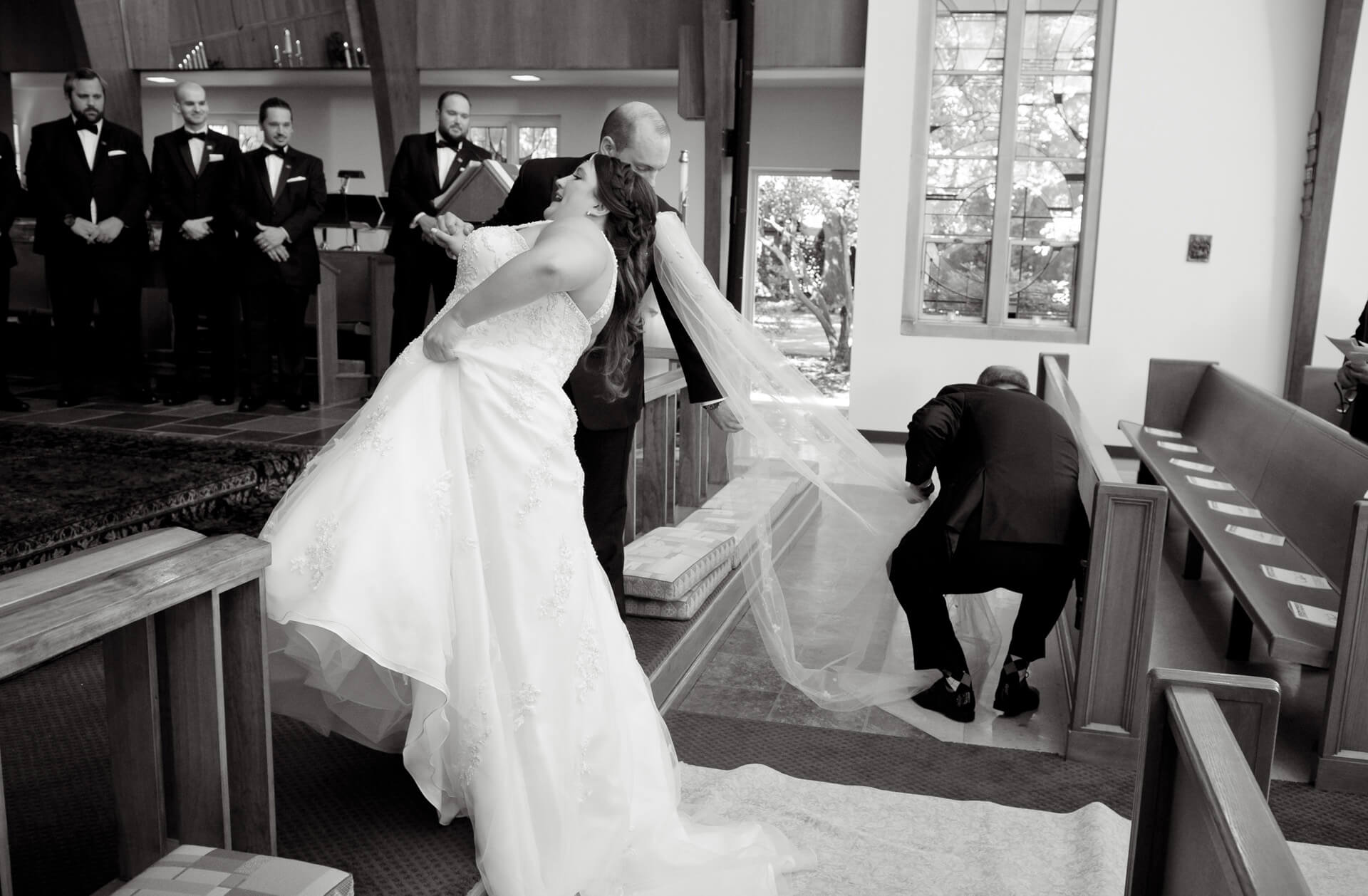 Documentary wedding photo of the bride's veil gets snagged on the floor as she climbs up to the altar in her Metro Detroit Michigan wedding.