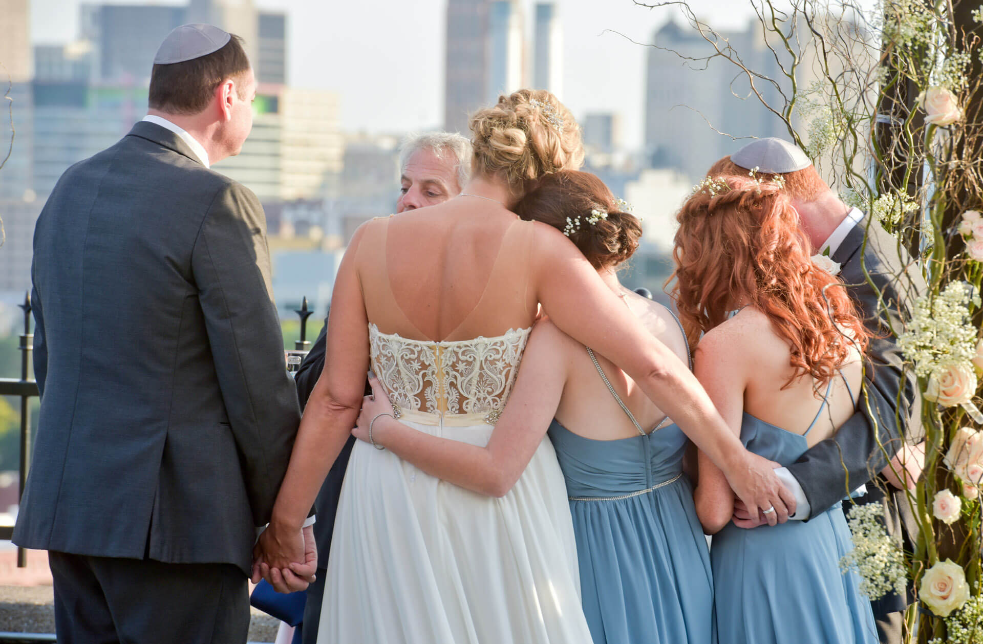 Documentary wedding photo of a new blended family during their Jewish ceremony on a rooftop in Detroit, Michigan.