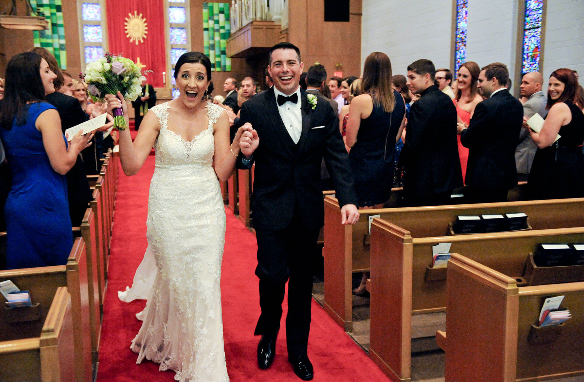 Documentary wedding photo of a bride and groom celebrating their walk back down the aisle at a church in Royal Oak, Michigan.