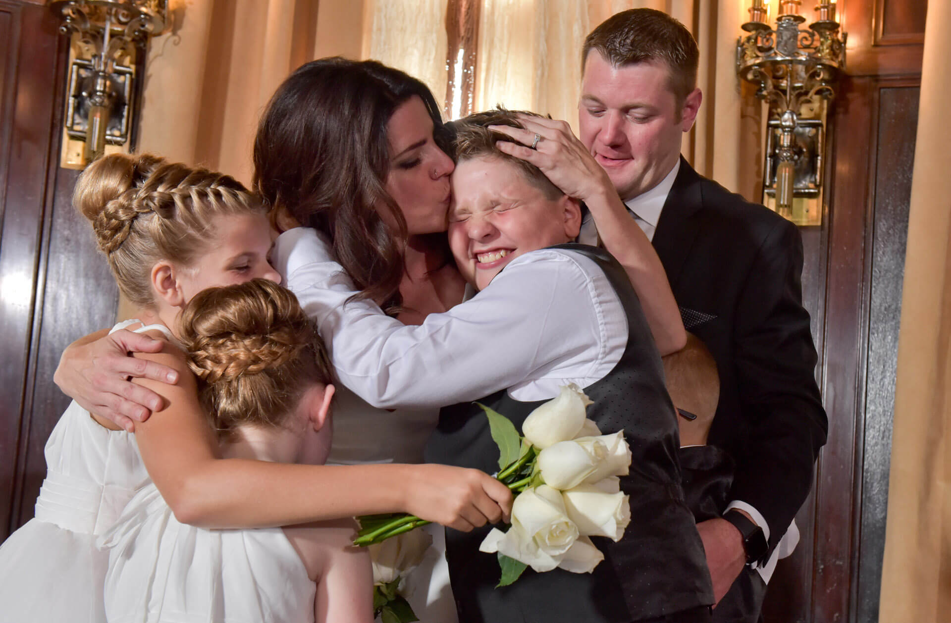 Documentary wedding photo of a mother kissing her new blended family after their Detroit wedding.