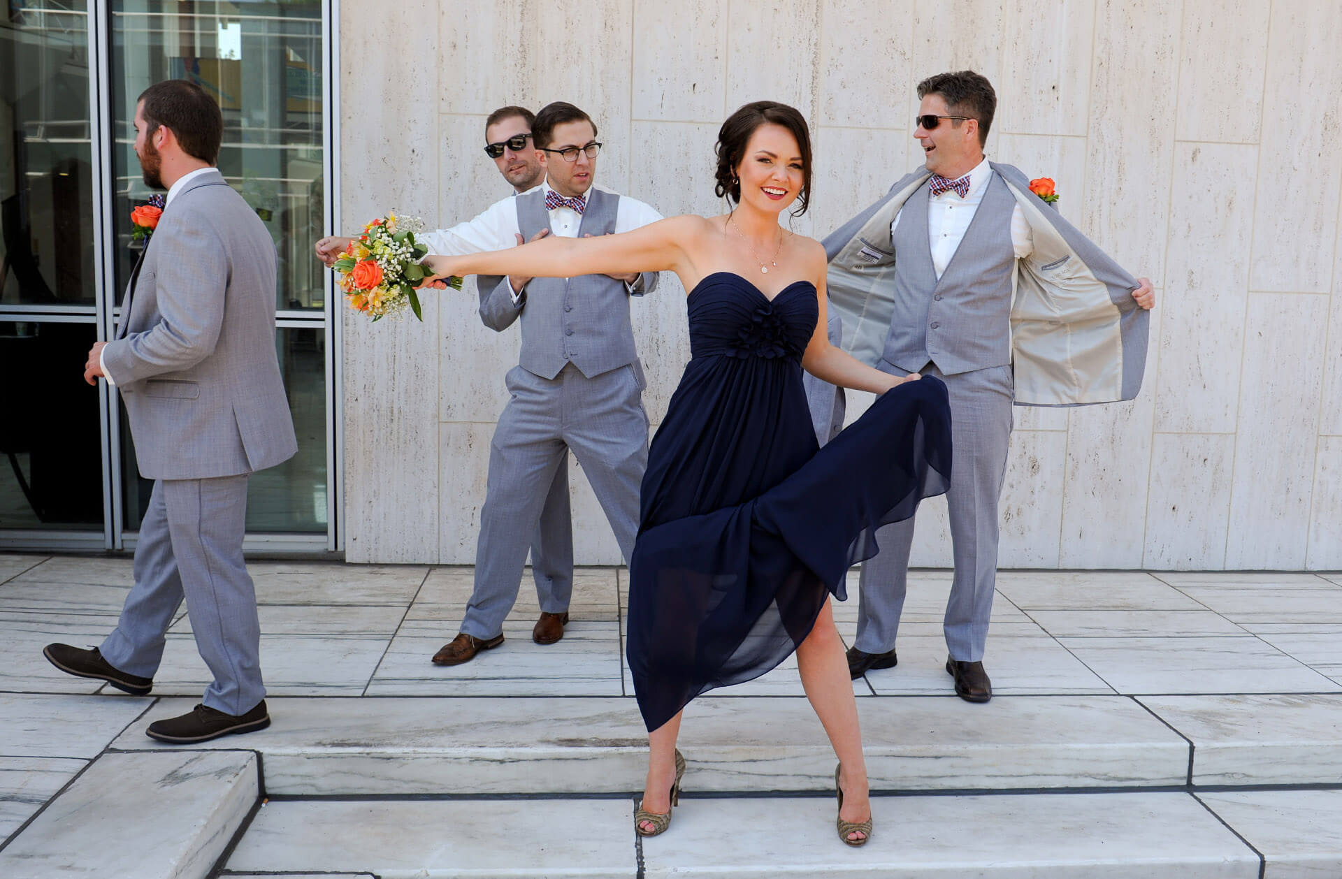 Documentary wedding photo of a bridesmaid taking full advantage of the breeze during a hot summer wedding in Detroit, Michigan.