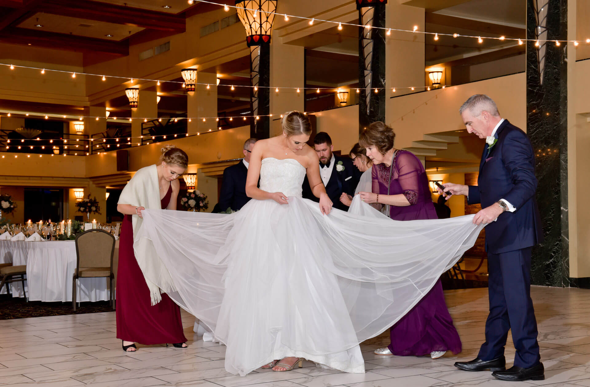 Documentary wedding photo of the bride's family all pitching in to figure out her bustle at her Atheneum Hotel in Detroit, Michigan.