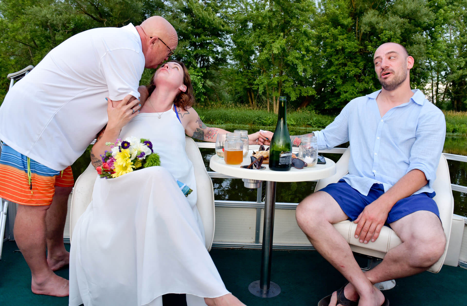 Documentary wedding photo of a father kissing his daughter while her new husband looks on after a backyard river wedding in Michigan.