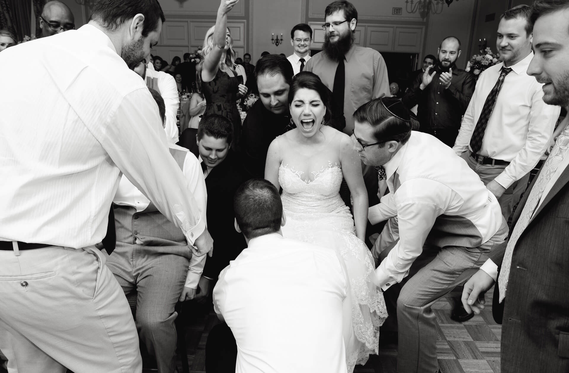 Documentary wedding photo of a bride about to be lifted for the Hora dance during a Jewish wedding in Detroit, Michigan.