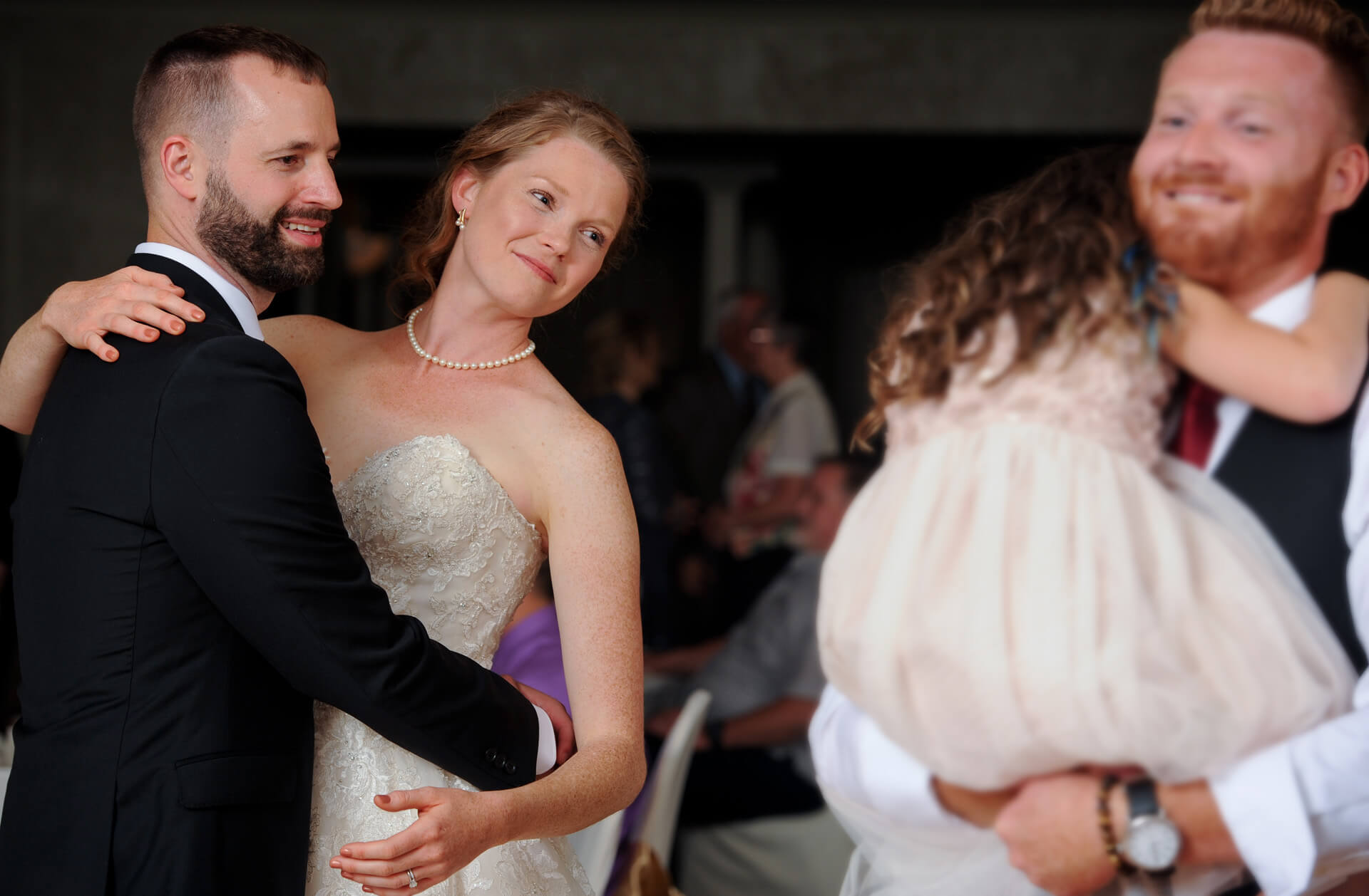 Documentary wedding photo of the bride and groom looking lovingly at the flower girl dancing with her father in Metro Detroit, Michigan.
