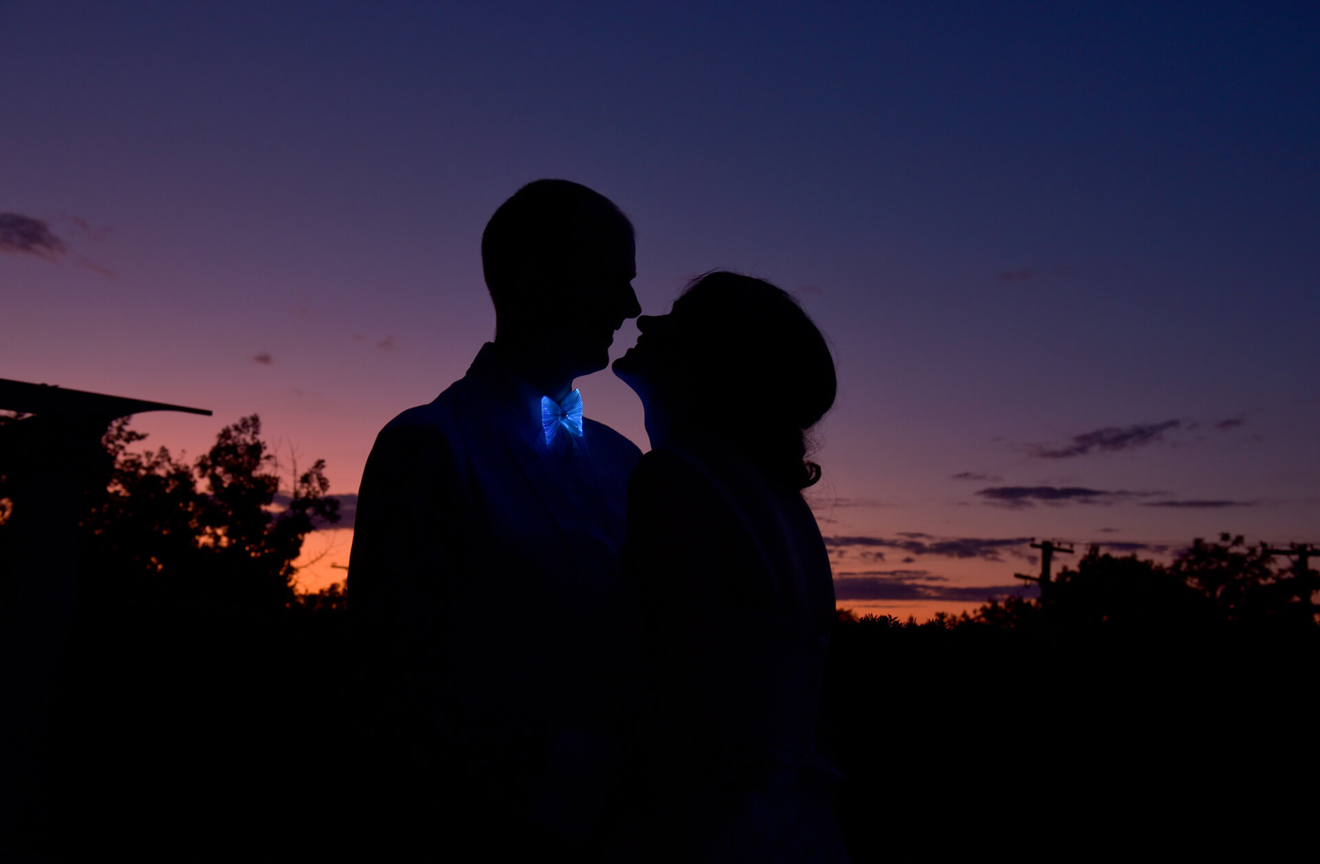 Epic Wedding portrait showing the bride and groom laughing at sunset showing off his silly glow in the dark tie e at their hotel in Ann Arbor, Michigan.