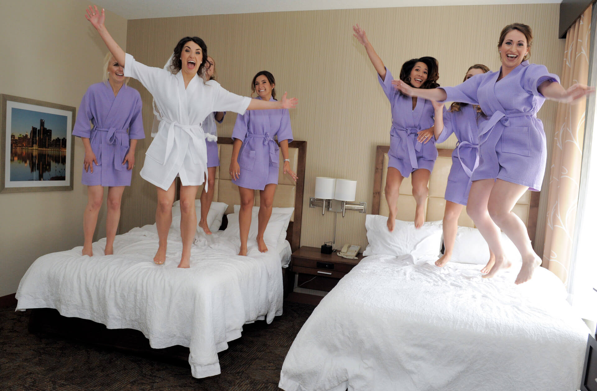 Epic Wedding portrait showing the bride and her wedding party jumping on the beds at their hotel in Metro Detroit, Michigan.