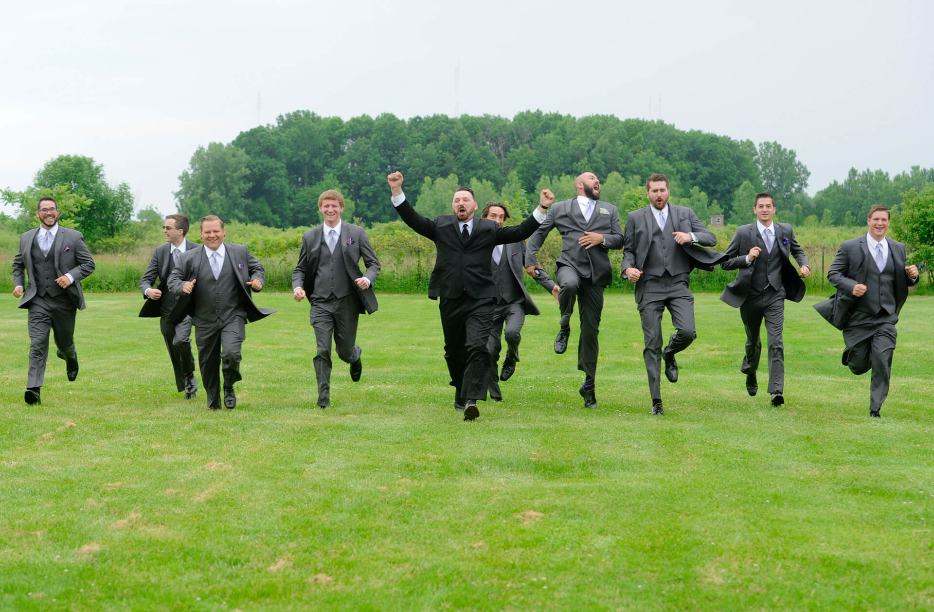 Epic Wedding portrait showing former track star groomsmen chasing each other in a field in Metro Detroit, Michigan.