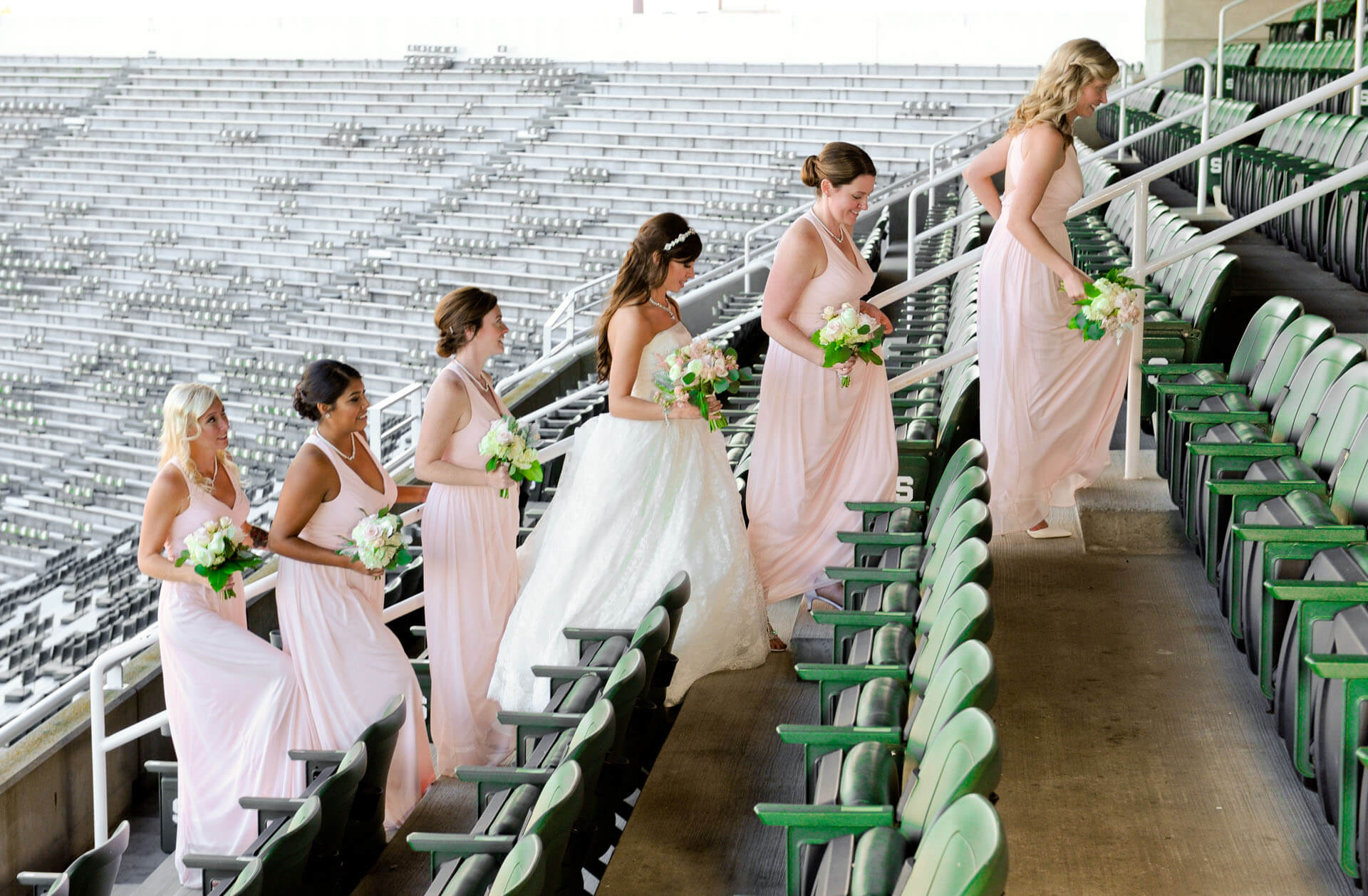 Epic Wedding portrait showing the bride and her bridesmaids heading back out of MSU's stadium during their wedding in East Lansing, Michigan.