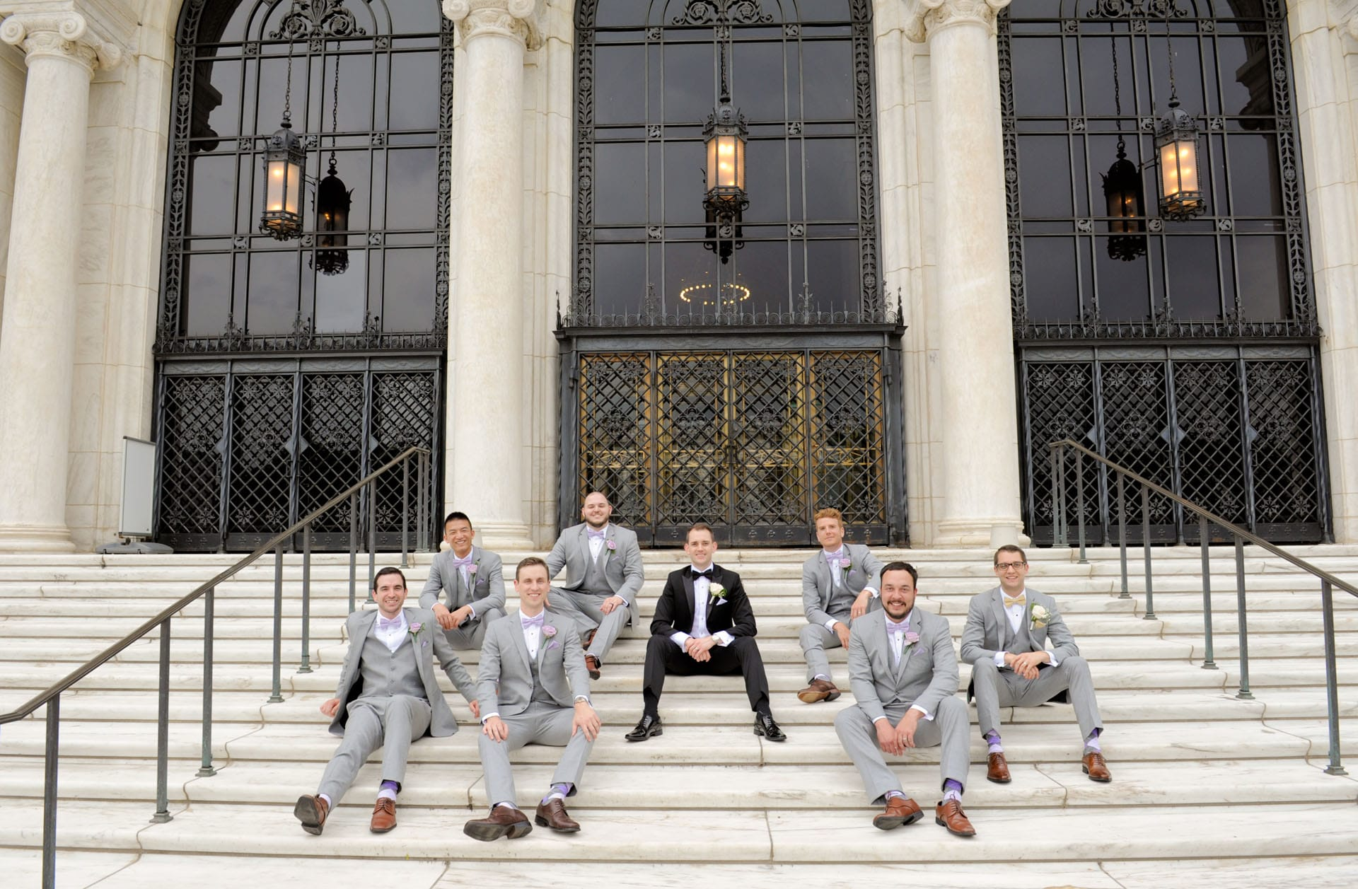 Epic Wedding portrait showing the groomsmen sitting in front of the DIA in Detroit, Michigan.