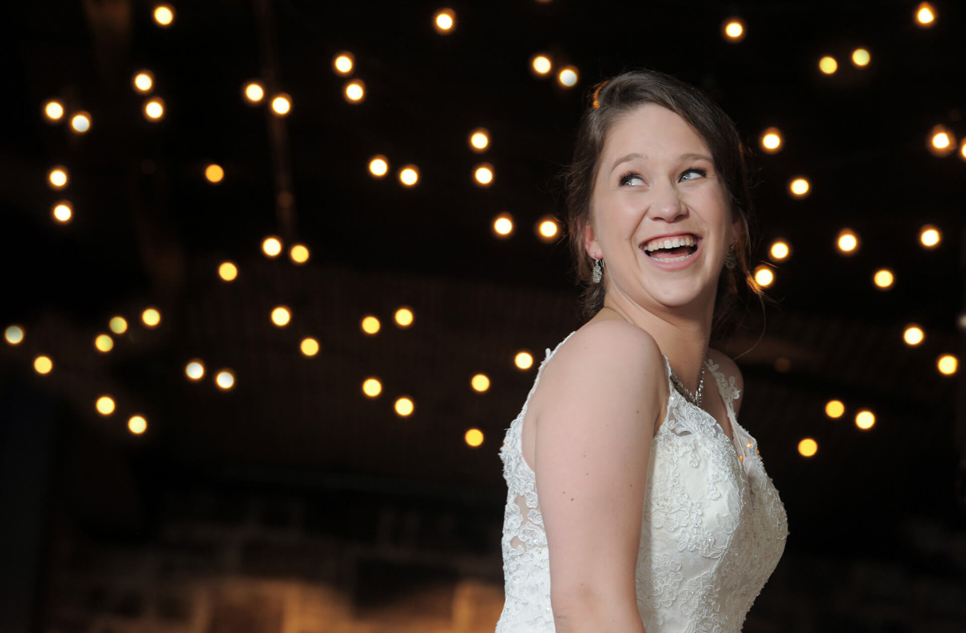 Epic Wedding portrait showing the bride laughing during her wedding at Weller's Raisin Room in Saline, Michigan.
