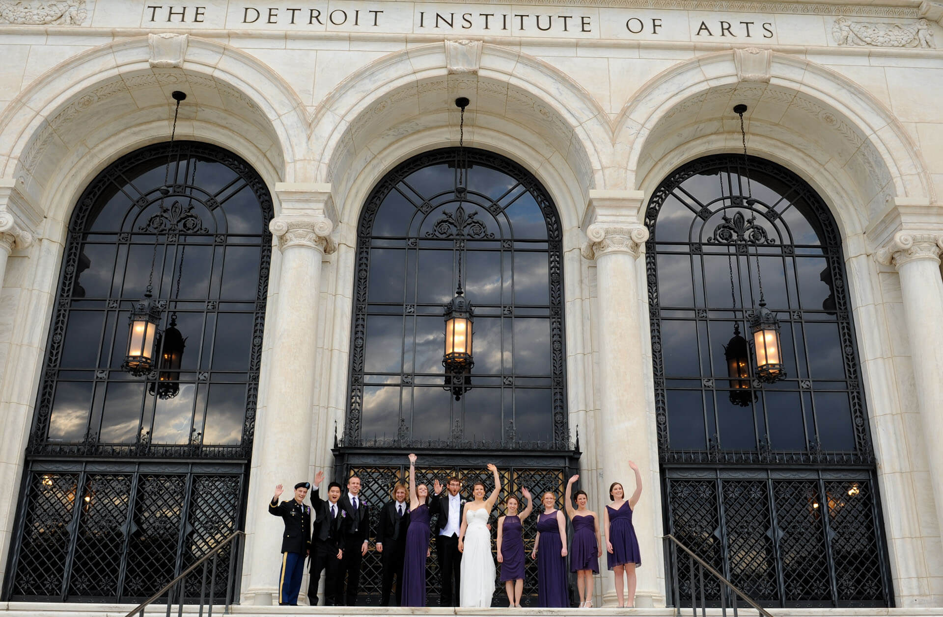 Epic Wedding portrait showing the bridal party standing on the steps of the DIA just as a car goes by and honks at them in Detroit, Michigan.
