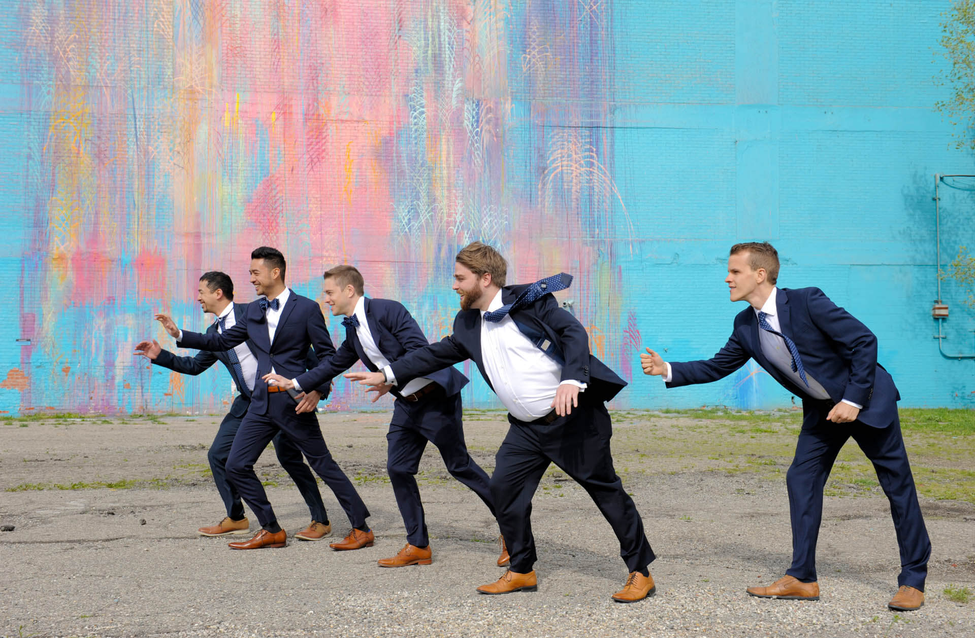 Epic Wedding portrait showing the groomsmen fighting the wind at the bleeding rainbow in downtown Detroit, Michigan.