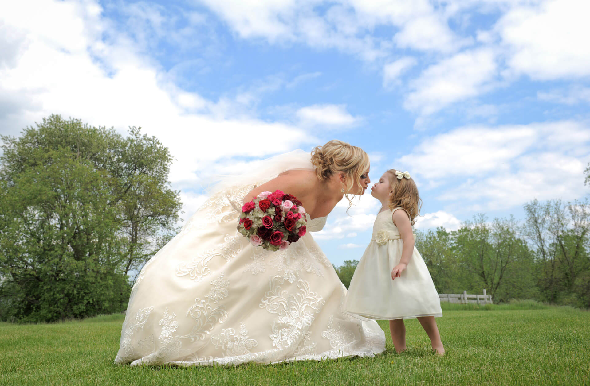 Epic Wedding portrait showing the bride getting smooched by a baby flower girl before her wedding in Troy, Michigan.
