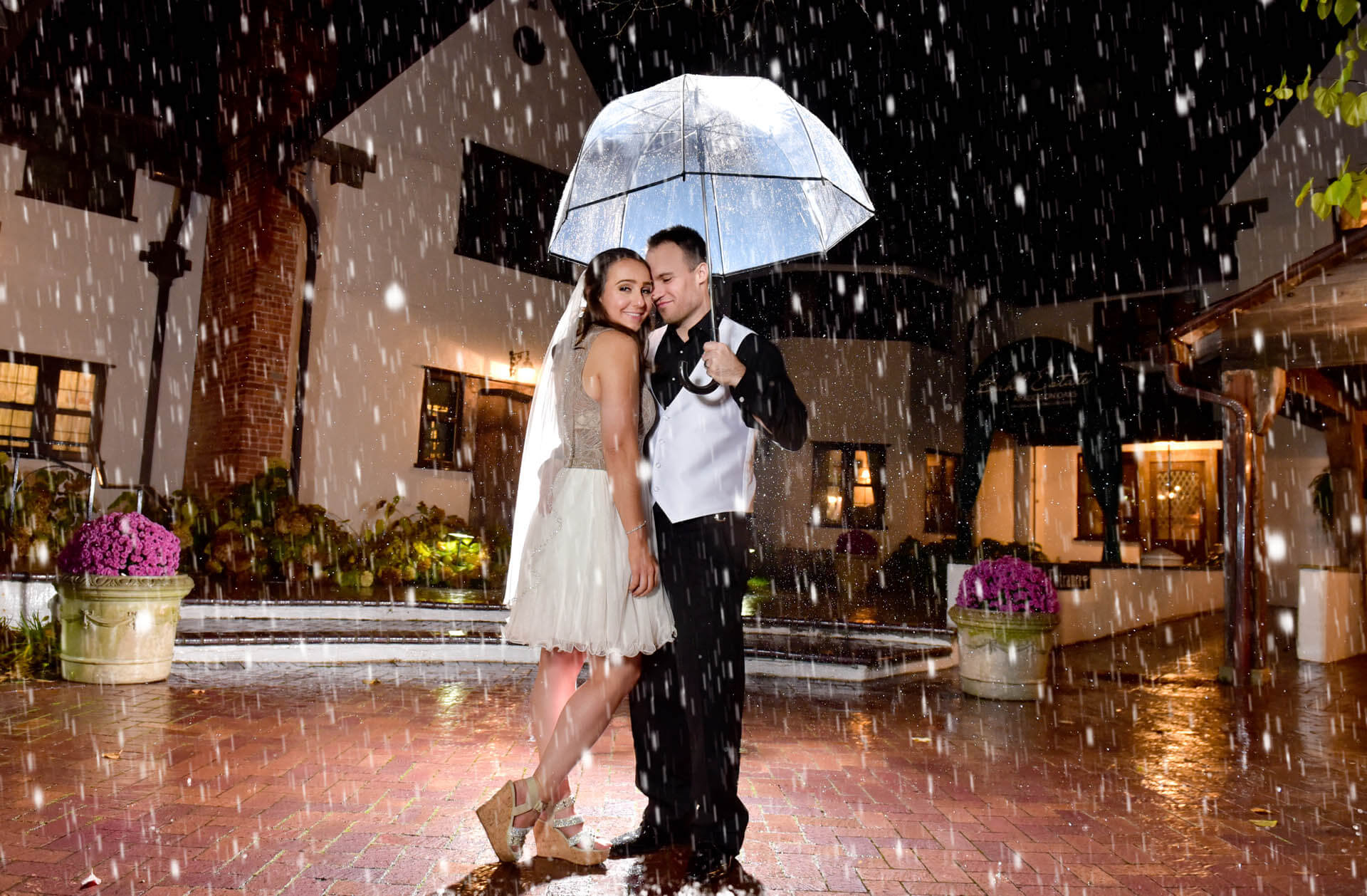 Epic Wedding portrait showing the bride and groom at the end of the wedding day in the rain at the Buhl Estates at Addison Oaks in Leonard, Michigan.
