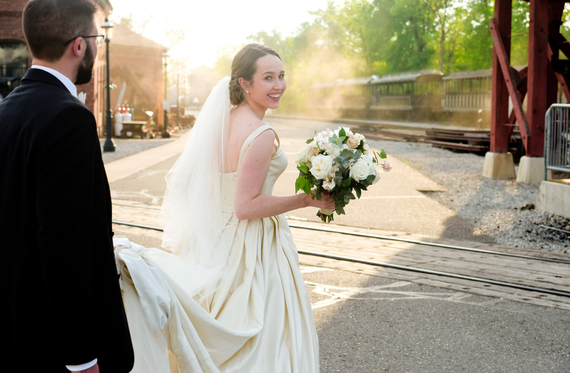 Epic Wedding portrait showing the bride walking through the Greenfield Villages with her husband after their wedding in Dearborn, Michigan.