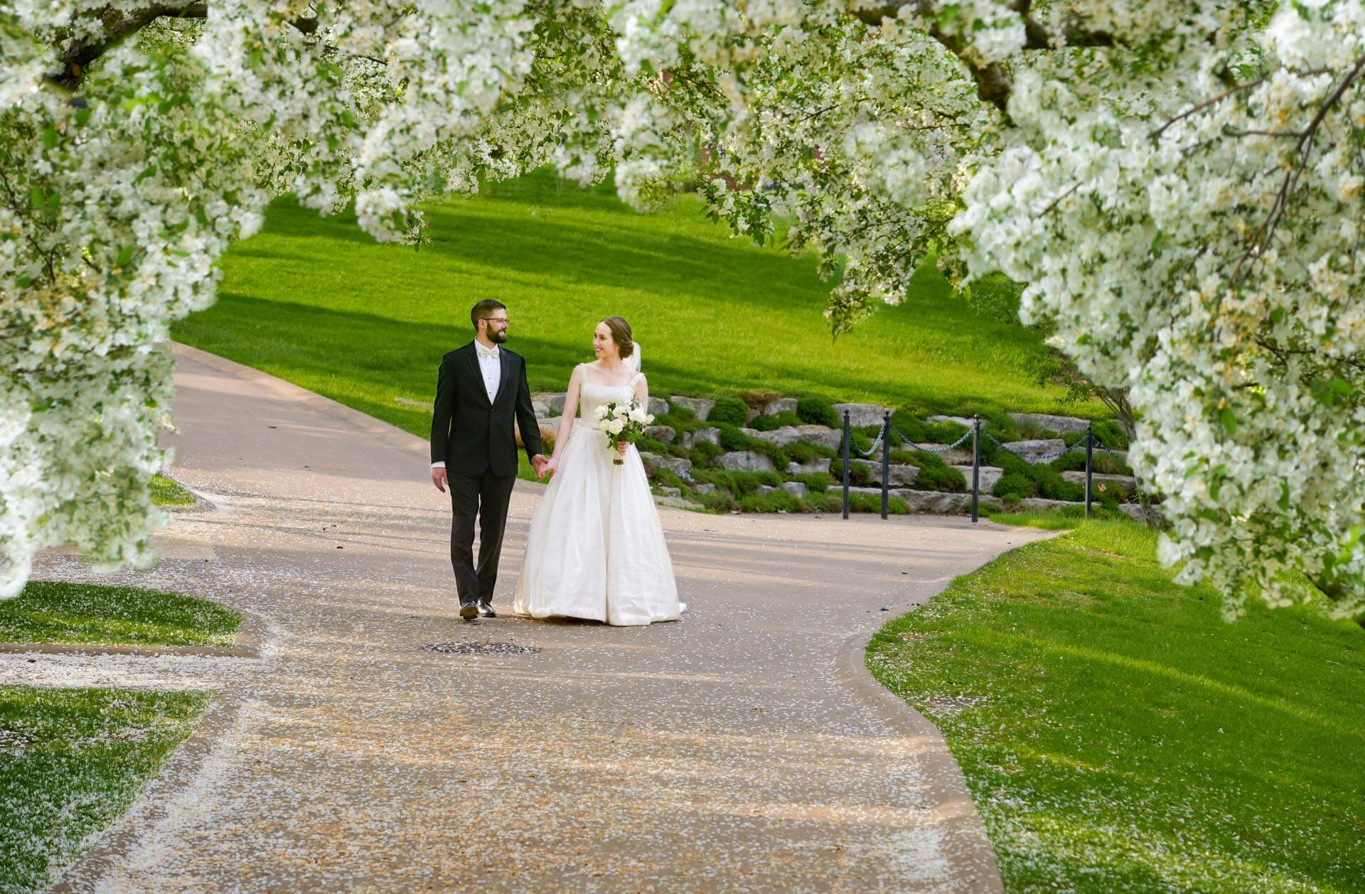 Epic Wedding portrait showing the bride walking through the Greenfield Village in Spring with her husband after their wedding in Dearborn, Michigan.