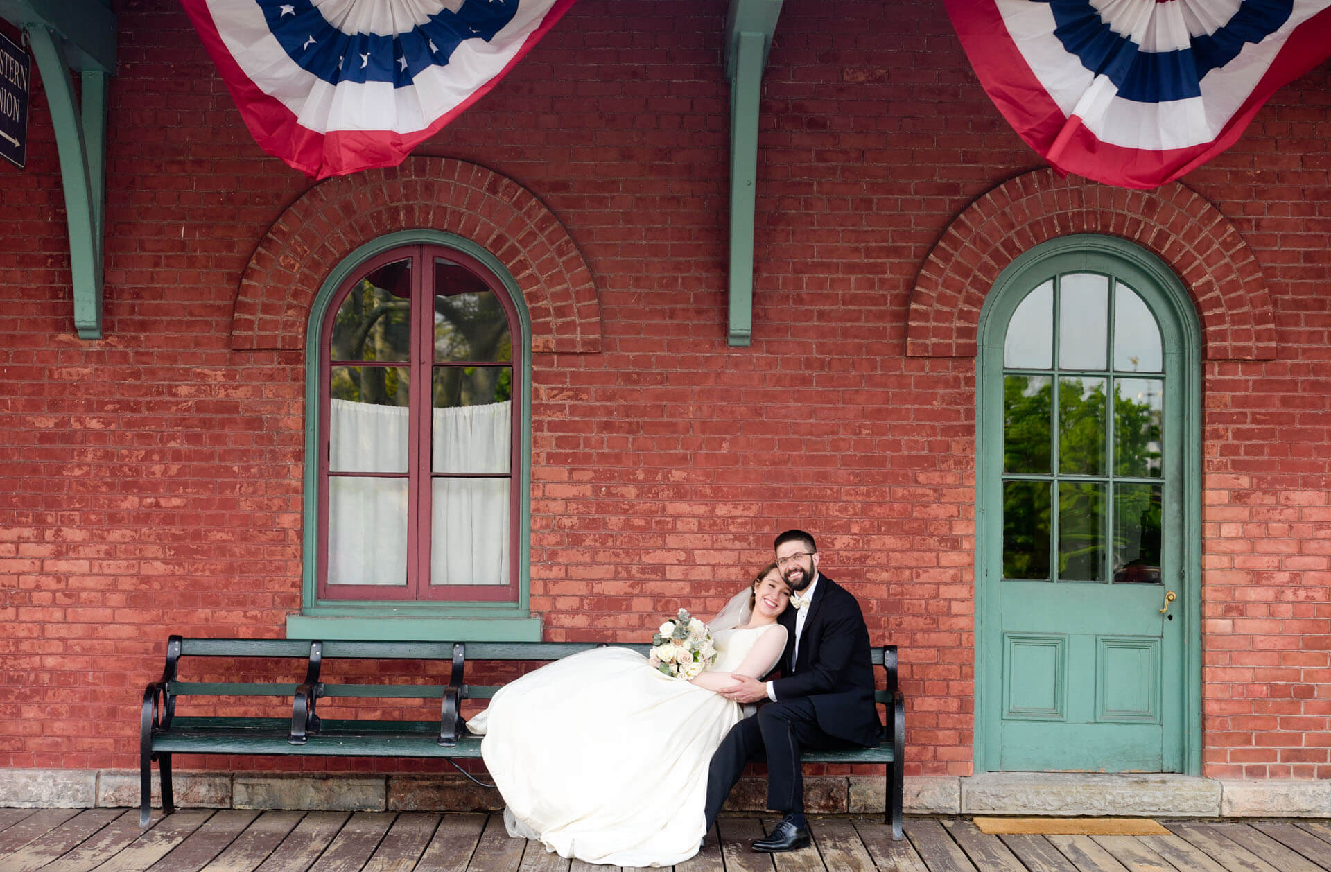 Epic Wedding portrait showing the bride and groom stretched out at the train station at the Greenfield Village in Spring with her husband after their wedding in Dearborn, Michigan.