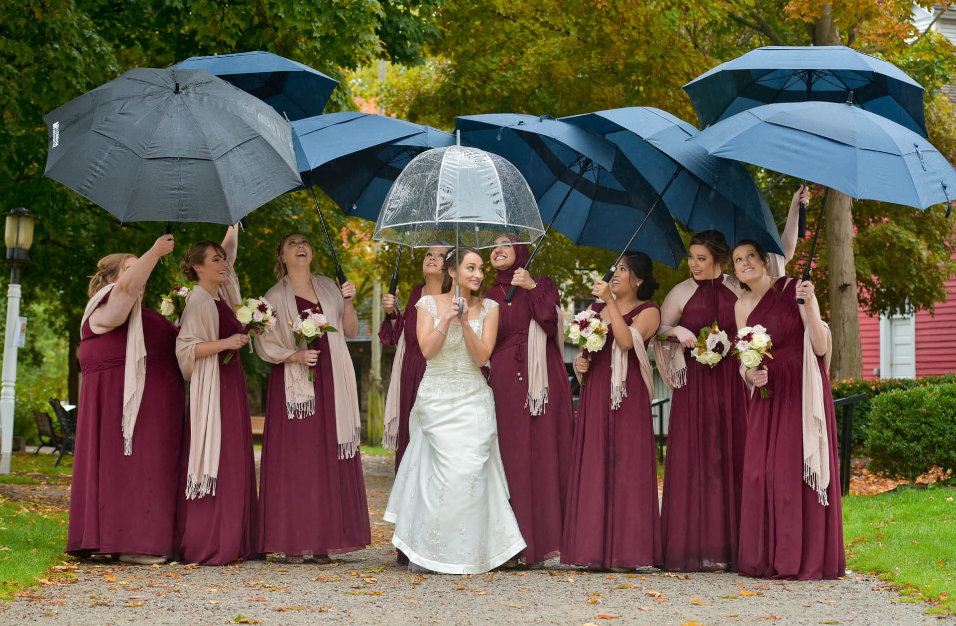 Epic Wedding portrait showing the bride and her maids of honor head out into the rain for some photos at Race Mills in Northville, Michigan.