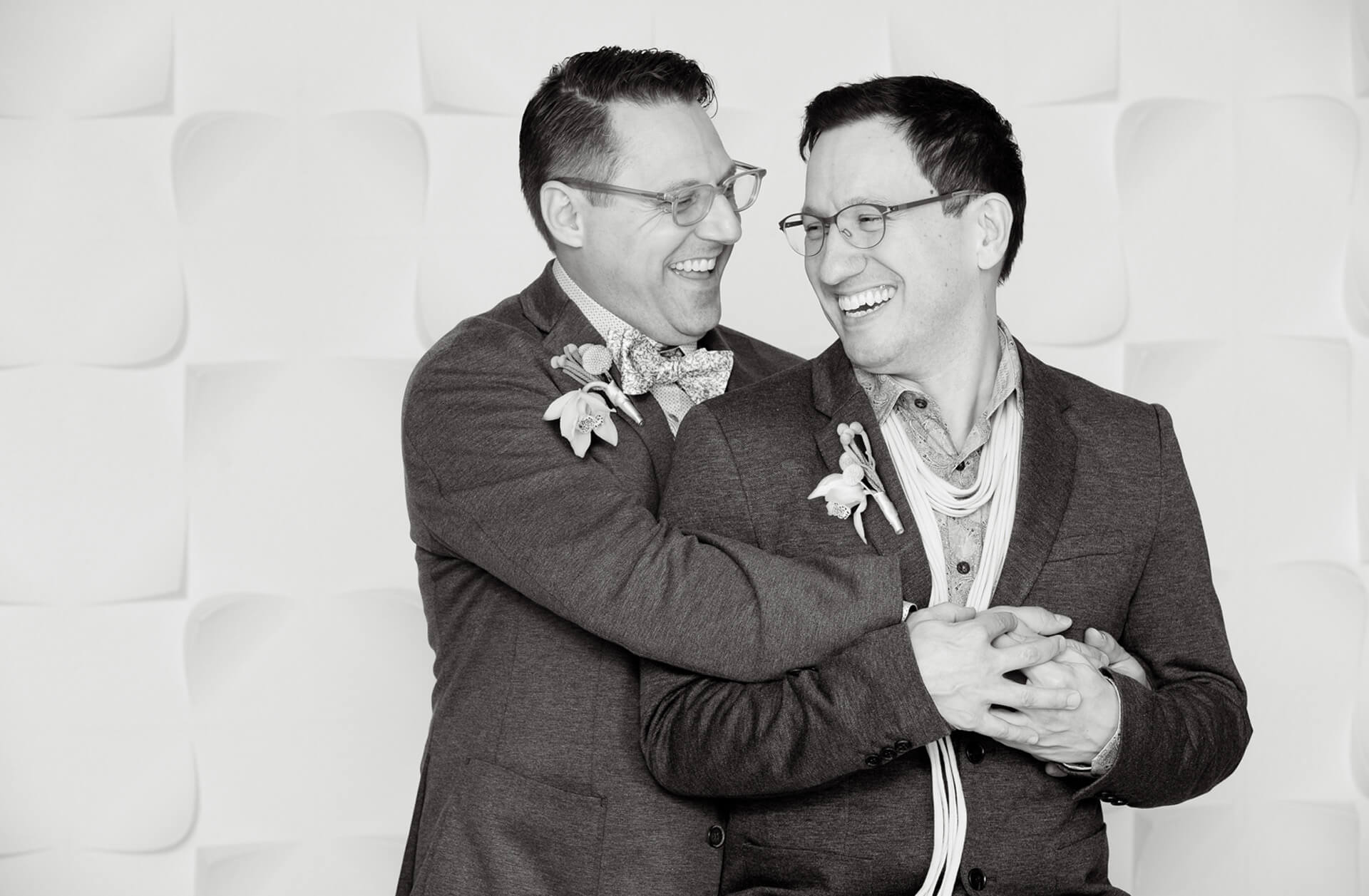Wedding photojournalist Marci Curtis captures moments during her wedding photography like these two men hugging after their wedding ceremony at home in Pleasant Ridge, Michigan.
