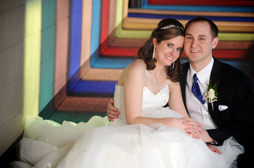A couple lay happily in their church's corridor after their Macomb, Michigan wedding.