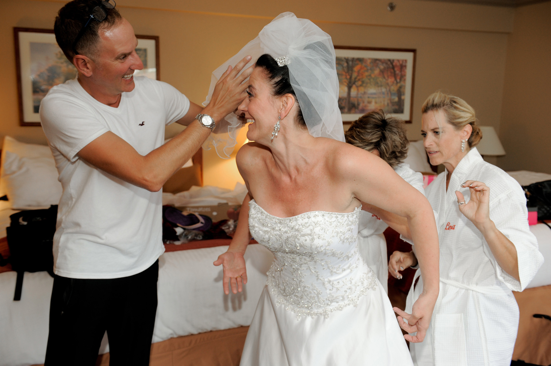 A family oriented wedding in Michigan showcases Michigan wedding photographer's photograph of the bride getting dressed with her Man of honor at her wedding at Wyndham Garden Hotel in Sterling Heights, Michigan (formerly known as the Sterling Inn).
