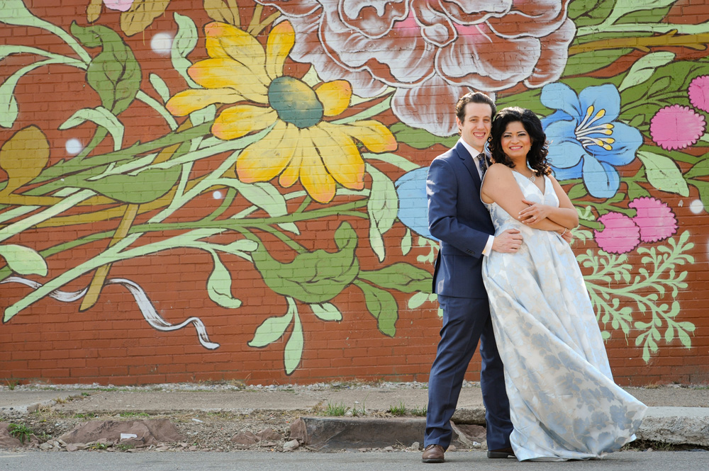 A Detroit wedding couple poses at Easter Market downtown Detroit, Michigan before their Masonic Temple wedding reception begins.