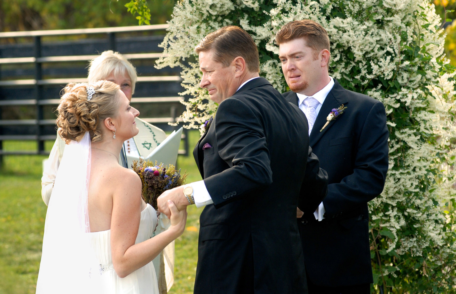 Favorite Michigan backyard wedding photography features photojournalist photos of  the emotional hand off of the bride to a visibly emotional groom during a wedding in metro Detroit, Michigan featuring their lovely backyard garden wedding in fall.