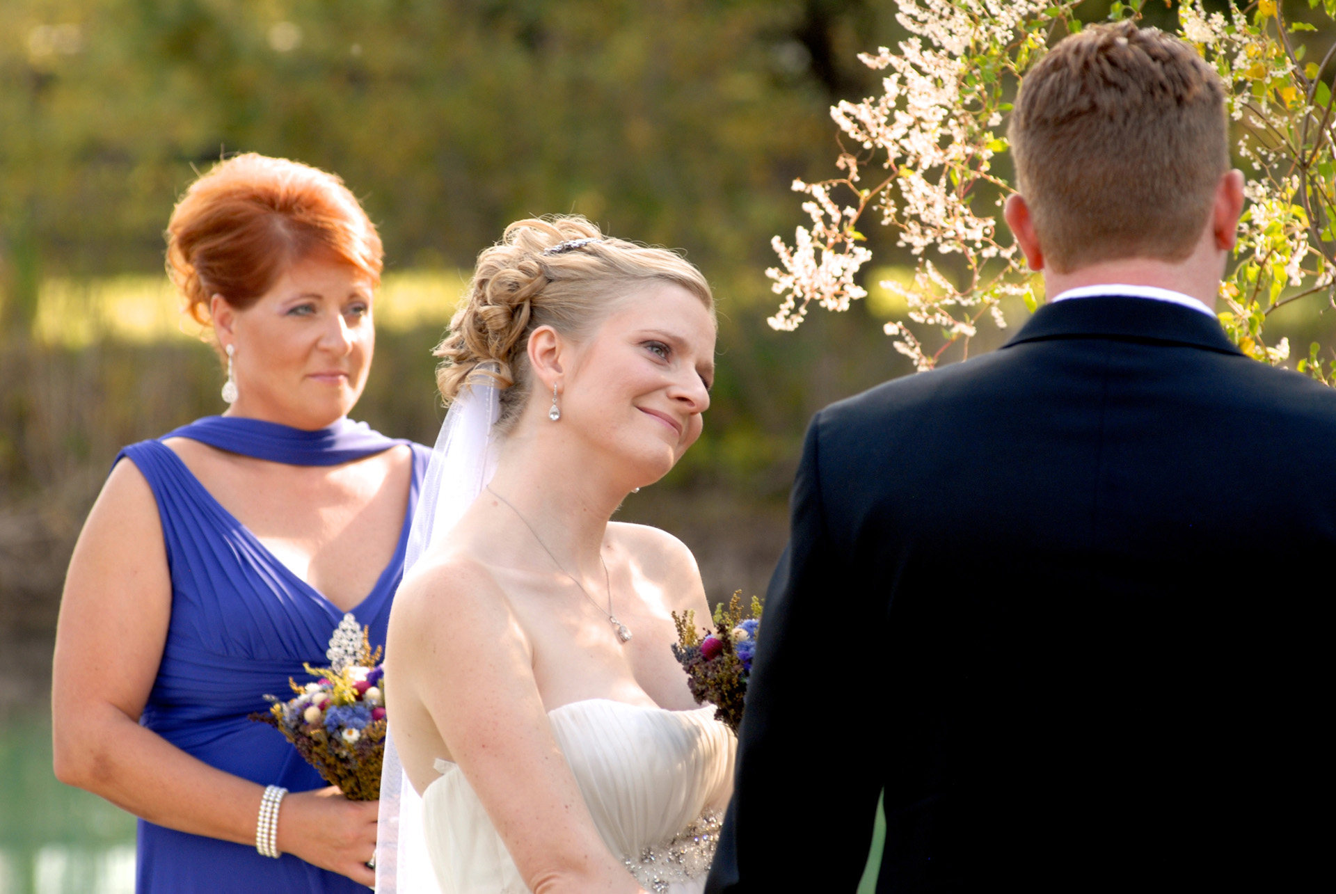 Best Michigan backyard wedding photography features photojournalist photos of  the bride listening to her groom's vows in metro Detroit, Michigan featuring their lovely backyard garden wedding in fall.
