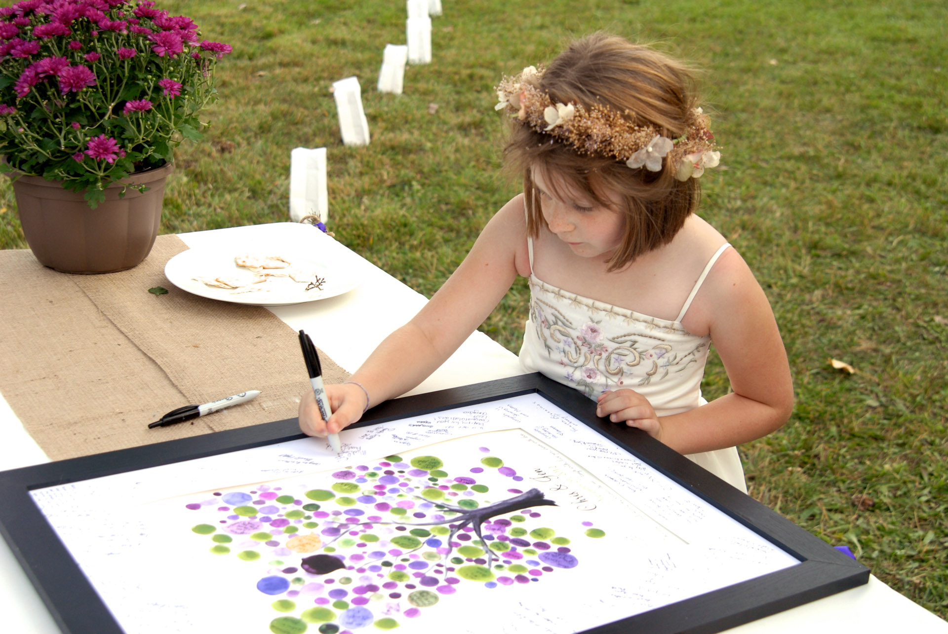 Best Michigan backyard wedding photography features photojournalist photos of the flower girl signing the guest book in metro Detroit, Michigan featuring their lovely backyard garden wedding in fall.