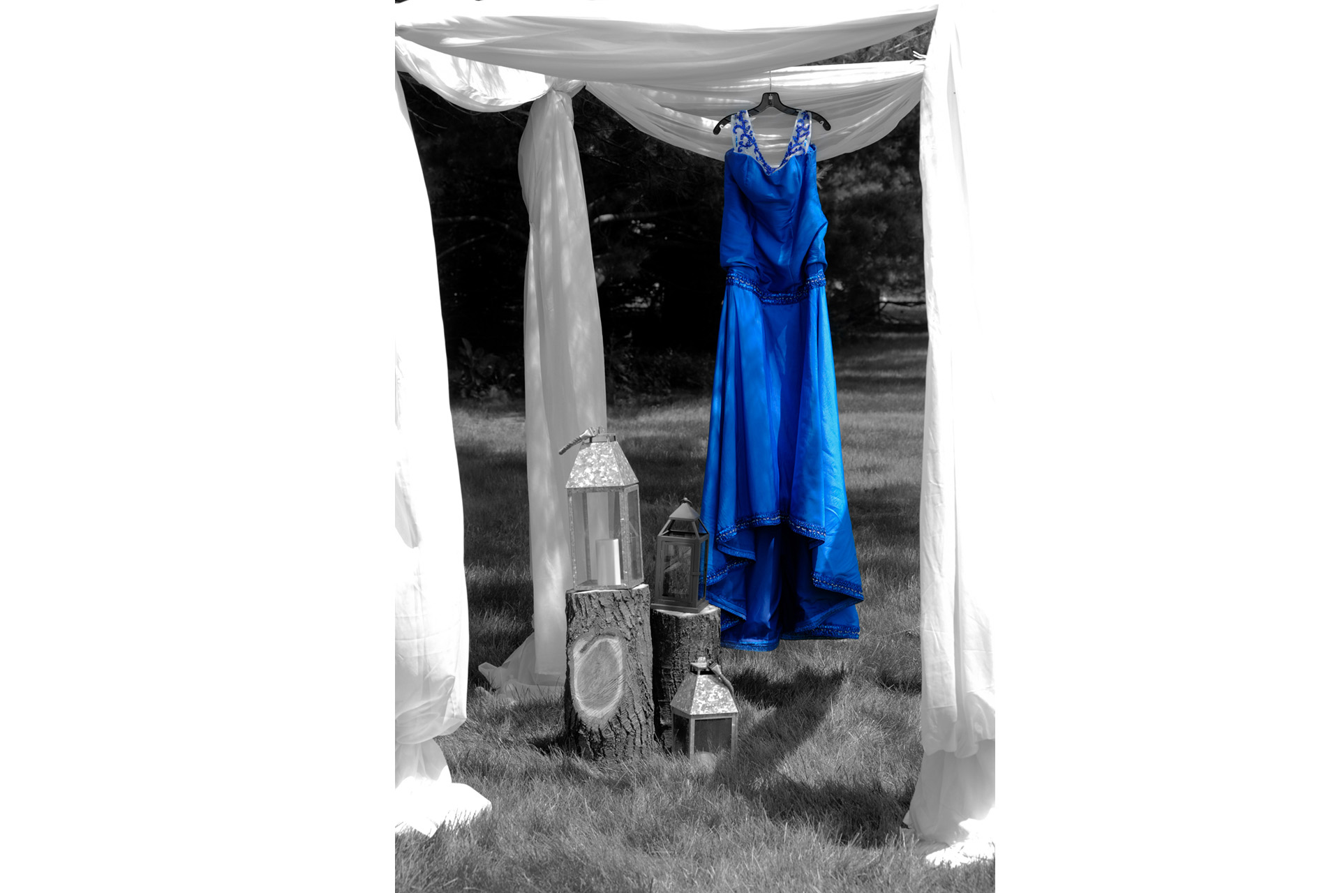budget conscience brides featuring contemporary and Pinterest worthy wedding photographs in Michigan highlights moving away from Pinterest to creating your unique wedding photography showing the bride's bright blue wedding dress hanging under the tent where the couple will exchange vows for their wedding at the Michigan wedding that emphasized photojournalist's moments and kept the bride on her budget.