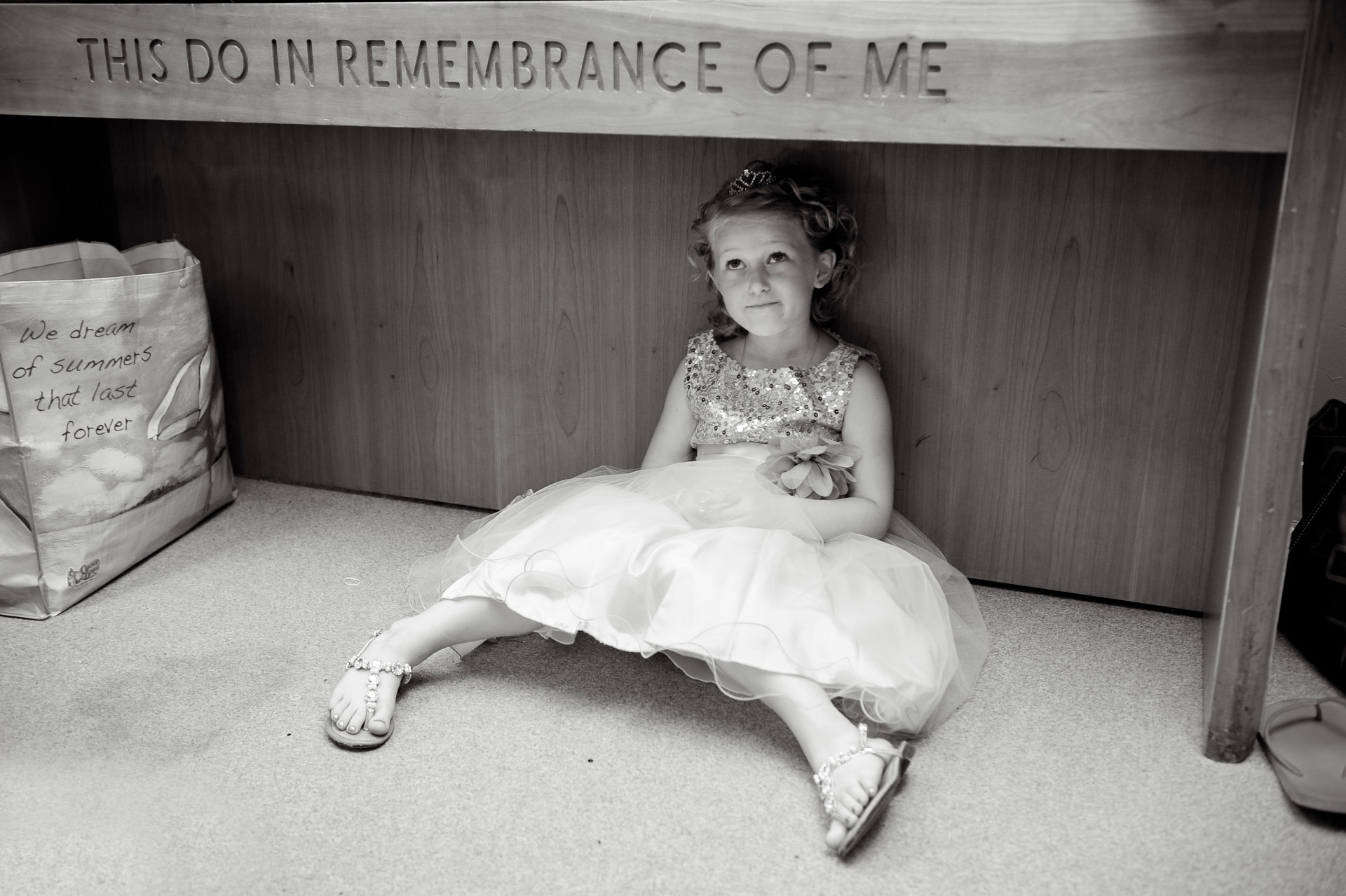 budget conscience brides featuring contemporary and Pinterest worthy wedding photographs in Michigan highlights moving away from Pinterest to creating your unique wedding photography showing the flower girl hiding below the altar before the Michigan wedding that emphasized photojournalist's moments and kept the bride on her budget.
