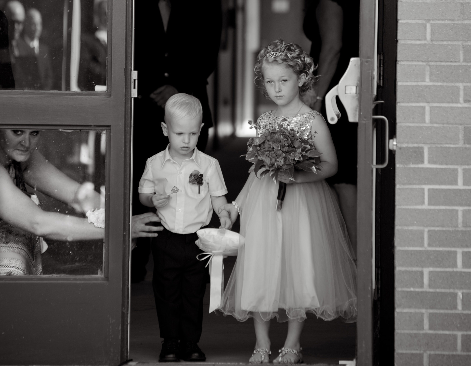 budget conscience brides featuring contemporary and Pinterest worthy wedding photographs in Michigan highlights moving away from Pinterest to creating your unique wedding photography showing the flower girl and the ring bearer getting lined up to start down the aisle at the Michigan wedding that emphasized photojournalist's moments and kept the bride on her budget.