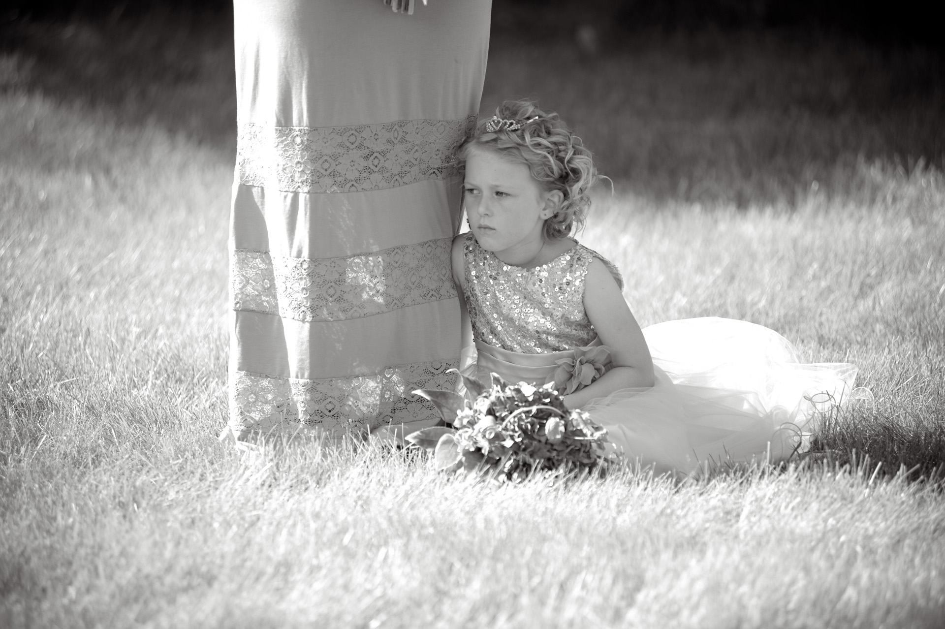 budget conscience brides featuring contemporary and Pinterest worthy wedding photographs in Michigan highlights moving away from Pinterest to creating your unique wedding photography showing the flower girl wilting and finding shade in her mother's shadow during a hot, outdoors Michigan wedding that emphasized photojournalist's moments and kept the bride on her budget.