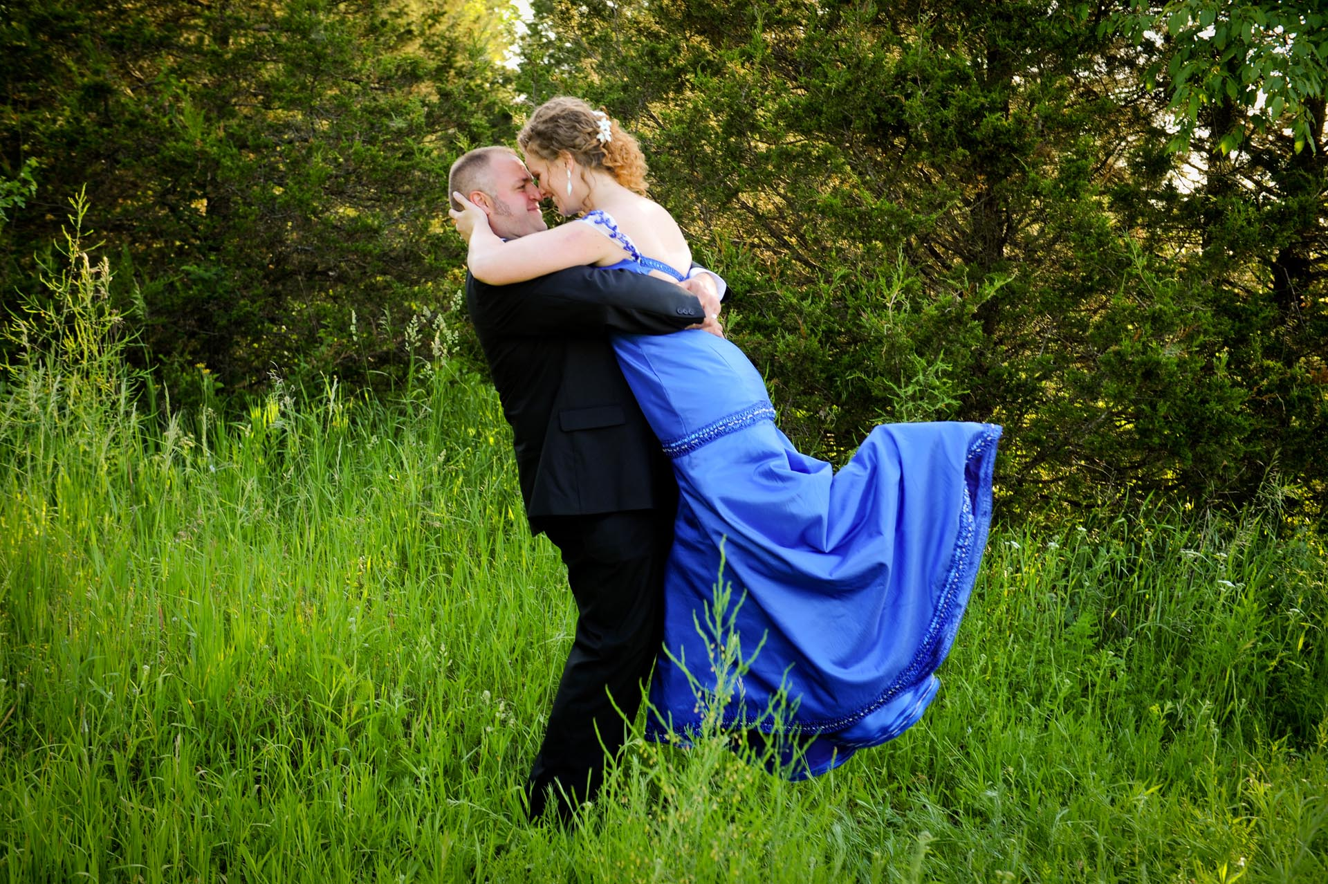 The budget conscience brides featuring contemporary and Pinterest worthy wedding photographs in Michigan highlights moving away from Pinterest to creating your unique wedding photography showing the bride and groom kissing in a field after their wedding at the Michigan wedding that emphasized photojournalist's moments and kept the bride on her budget.
