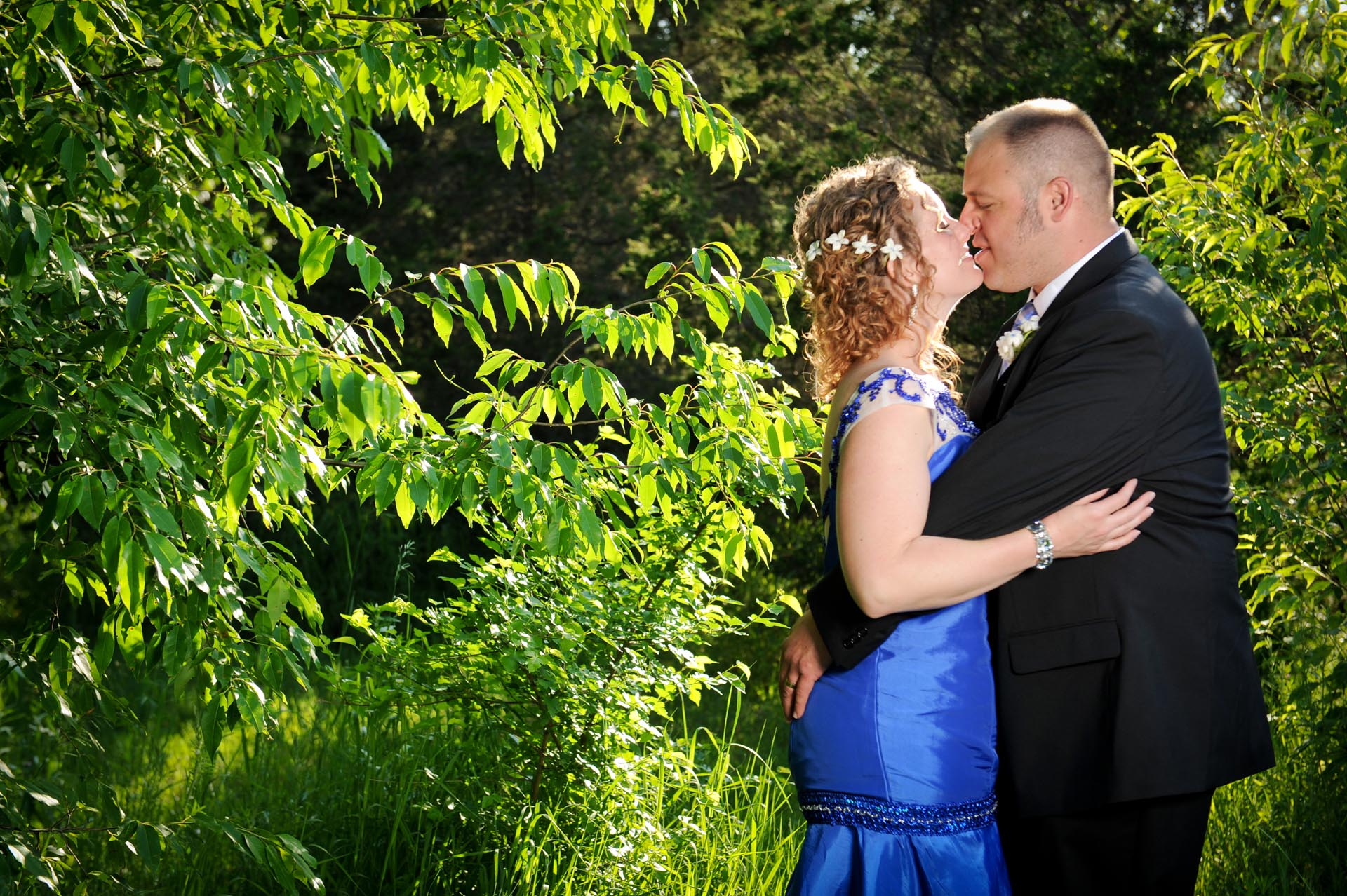 The budget conscience brides featuring contemporary and Pinterest worthy wedding photographs in Michigan highlights moving away from Pinterest to creating your unique wedding photography showing the bride and groom kissing in the woods after their Michigan wedding that emphasized photojournalist's moments and kept the bride on her budget.