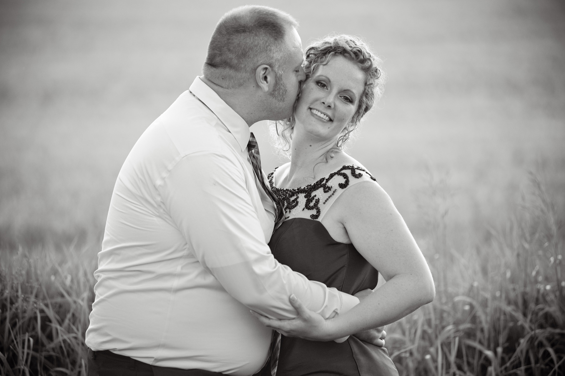 The budget conscience brides featuring contemporary and Pinterest worthy wedding photographs in Michigan highlights moving away from Pinterest to creating your unique wedding photography showing the bride and groom smooching in a field after their Michigan wedding that emphasized photojournalist's moments and kept the bride on her budget.