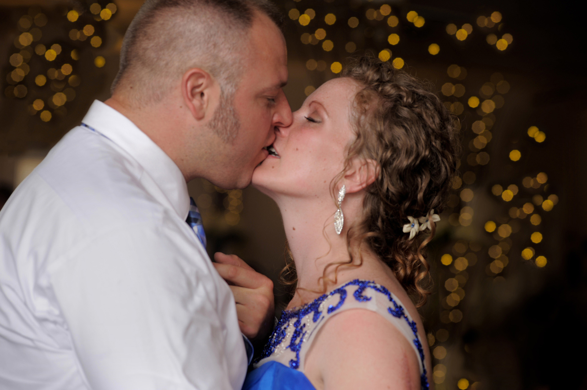 The budget conscience brides featuring contemporary and Pinterest worthy wedding photographs in Michigan highlights moving away from Pinterest to creating your unique wedding photography showing the bride and groom kissing during their wedding reception at the Michigan wedding that emphasized photojournalist's moments and kept the bride on her budget.