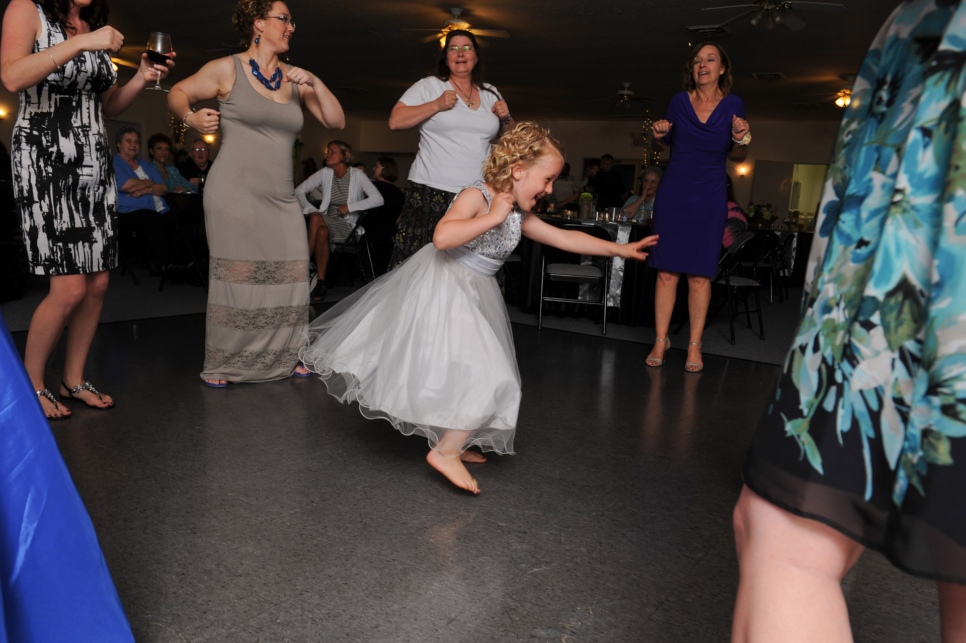 The budget conscience brides featuring contemporary and Pinterest worthy wedding photographs in Michigan highlights moving away from Pinterest to creating your unique wedding photography showing the flower girl dancing in the center of the guests during a wedding at the Michigan wedding that emphasized photojournalist's moments and kept the bride on her budget.
