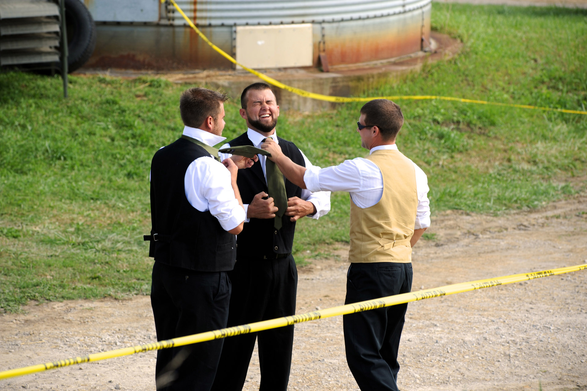 A farm wedding in Michigan shows the groom helping a groomsman adjust his tie at a Michigan country wedding.