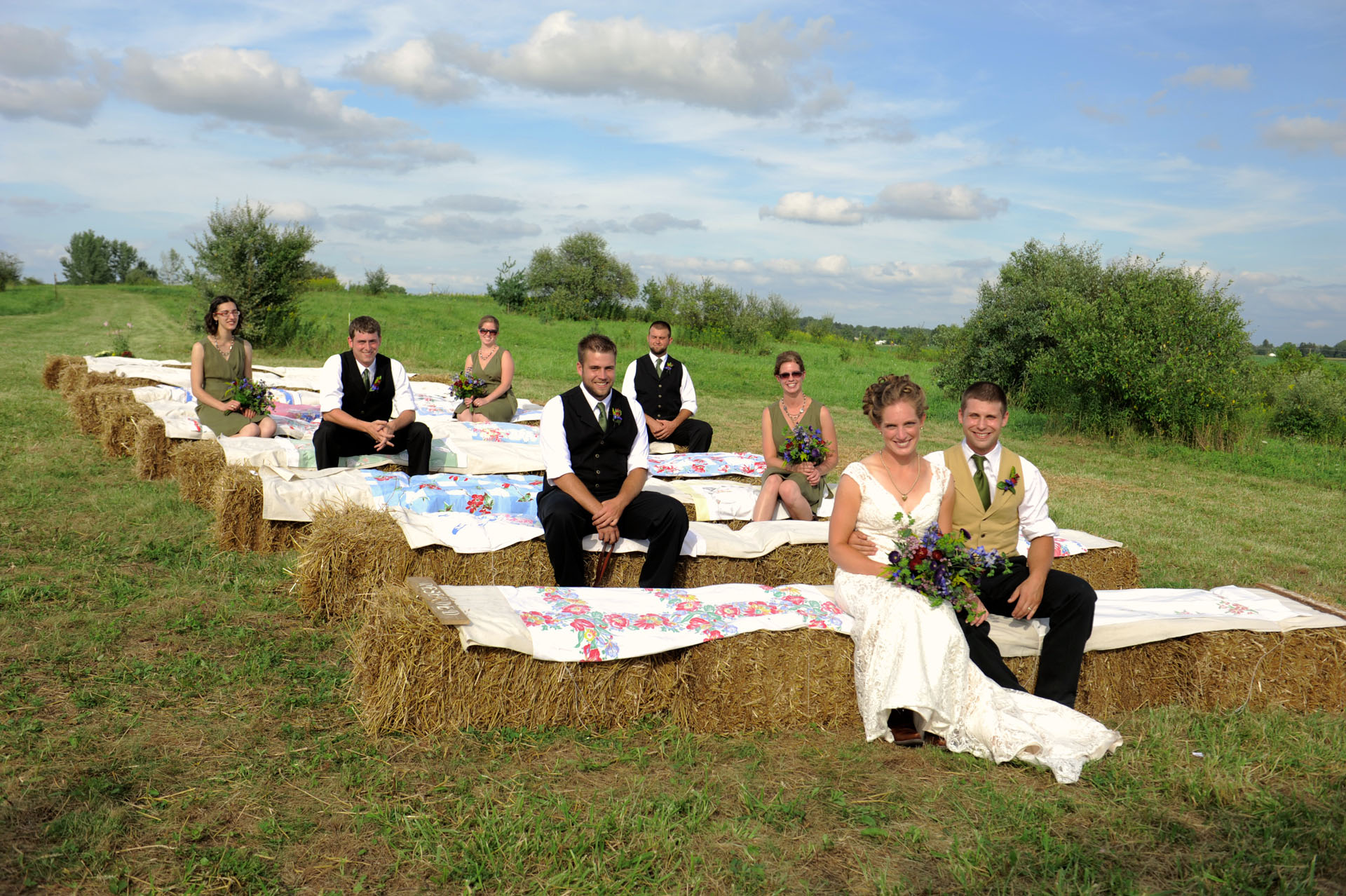 Michigan country wedding wedding photographer took a photo of the wedding party sitting on the covered hay bales their guests had been sitting on minutes beforehand at a Michigan country wedding.