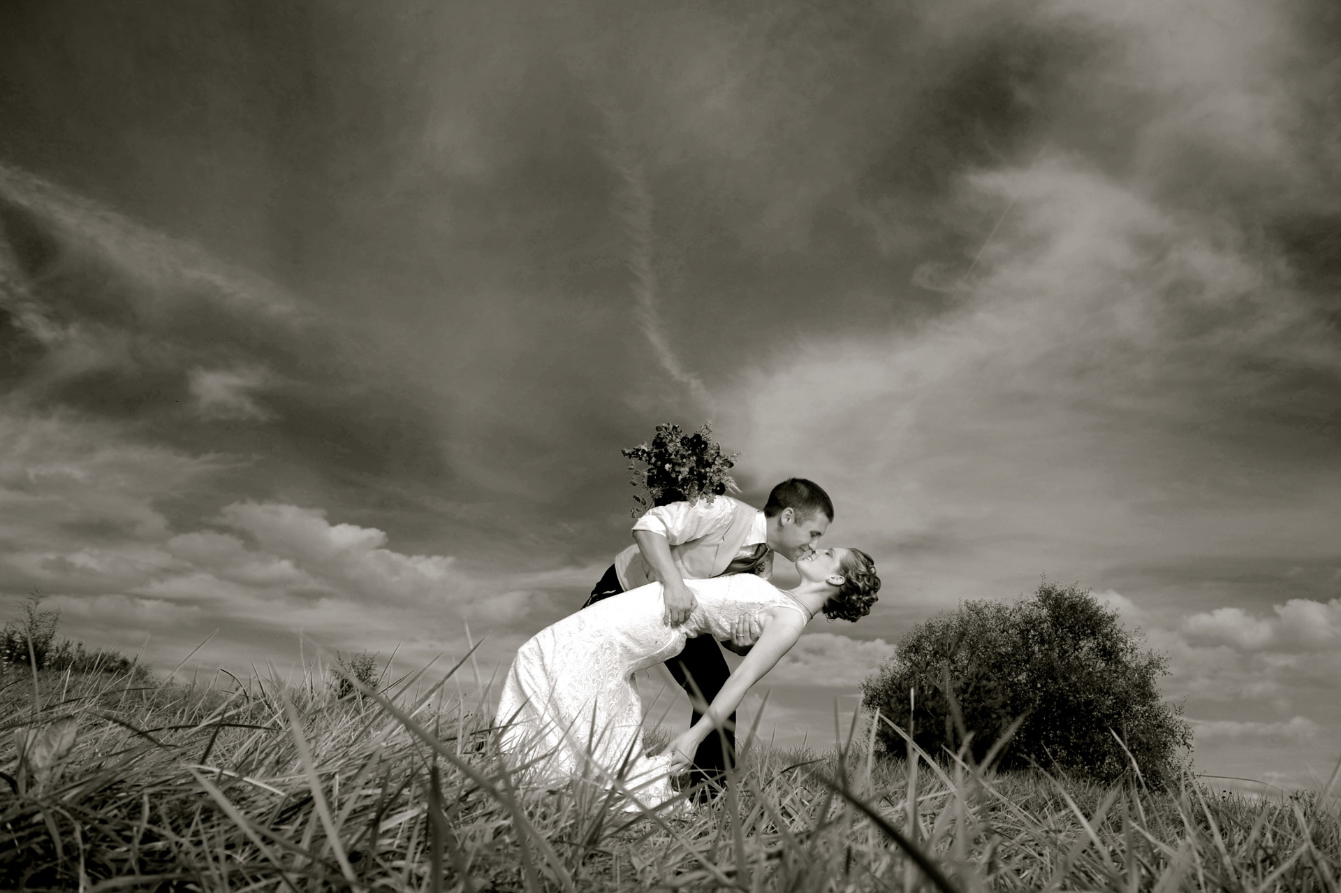 A farm wedding in Michigan features a couple doing a fabulous dip making the blue sky even more dramatic in this B&W photo at the Michigan country wedding.