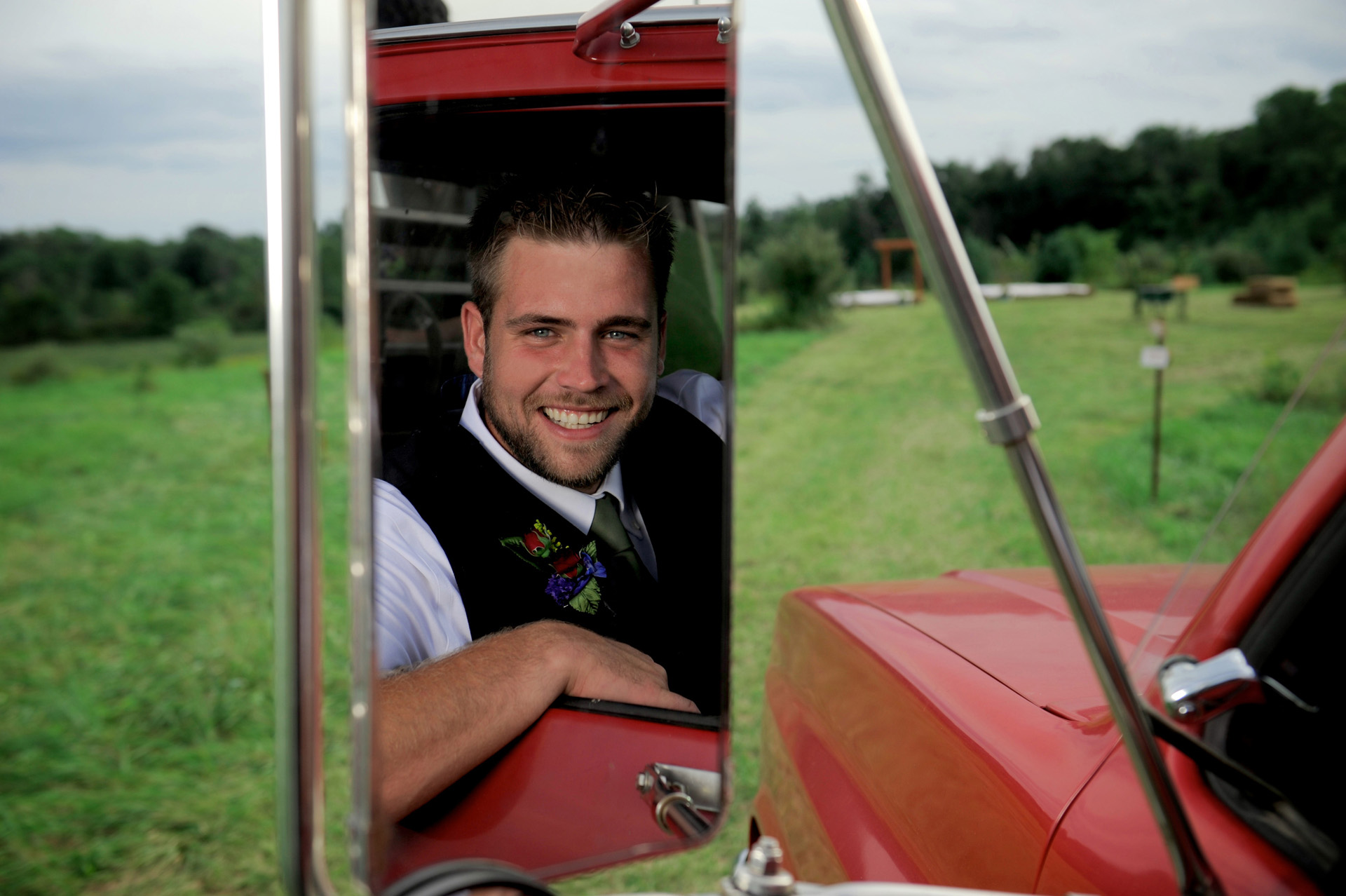 Michigan country wedding wedding photographer's photo of a groomsman in the side mirror of a pick up during a Michigan country wedding.